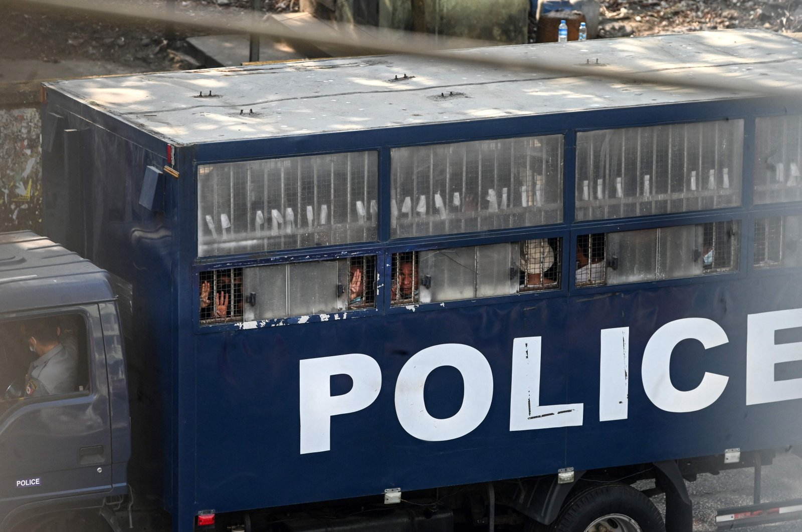 Protesters make the three-finger salute from a police truck in Yangon after a crackdown on demonstrations against the military coup, Yangon, Myanmar, Feb. 27, 2021. (AFP Photo)