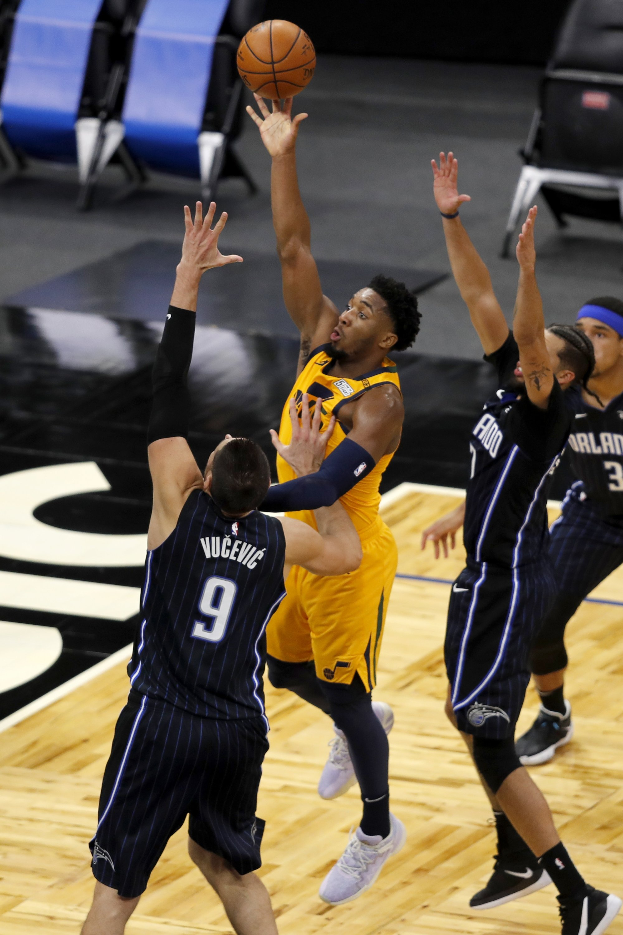 Guard Utah Jazz Donovan Mitchell (tengah) di Orlando Magic Center dalam pertandingan NBA di bawah tekanan Nicola Vusevic (kiri) dan guard Michael Carter-Williams (kanan), Orlando, Florida, 27 Februari 2021. (Foto AP)