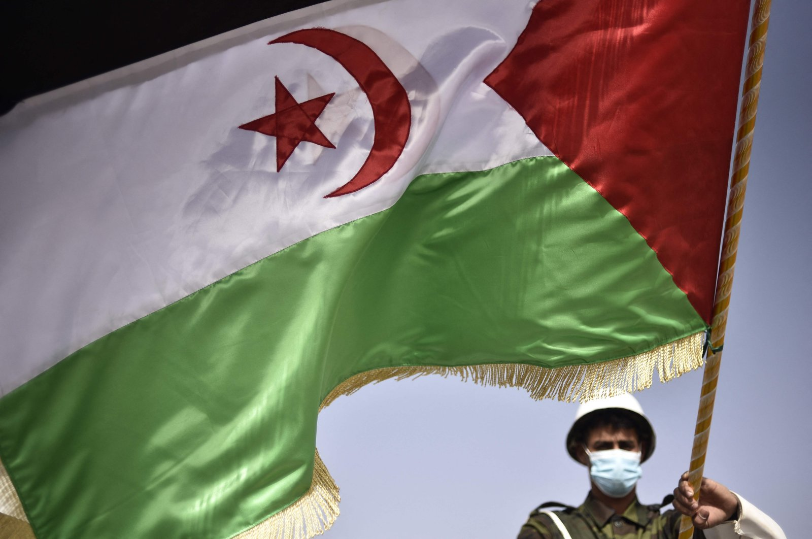 A Sahrawi soldier waves the Sahrawi flag during a parade marking the 45th anniversary of the declaration of the self-declared Sahrawi Arab Democratic Republic (SDAR), at a refugee camp on the outskirts of Tindouf, Algeria, on Feb. 27, 2021. (AFP Photo)