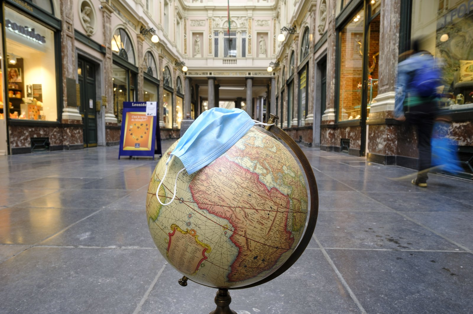 A globe with a surgical mask is seen on the floor of the Galeries Royales Saint-Hubert, Brussels, Belgium, Oct. 28, 2020. (Photo by Getty Images)