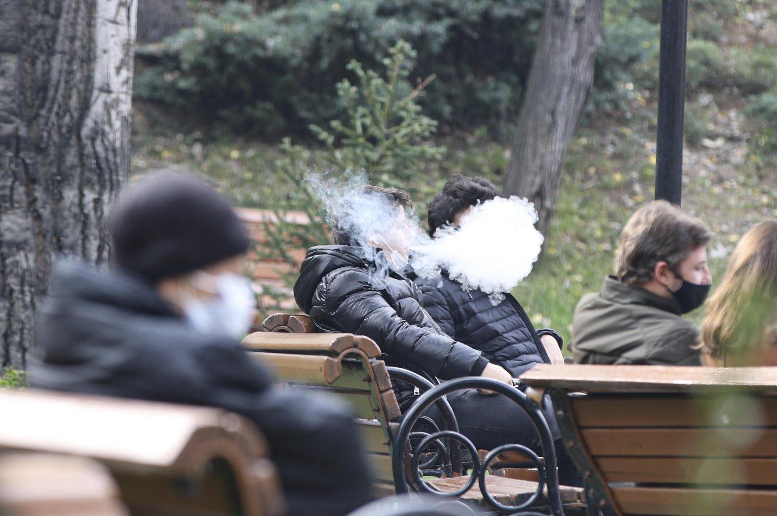 People smoke electronic cigarettes at a park in the capital Ankara, Turkey, Nov. 16, 2020. (DHA PHOTO)