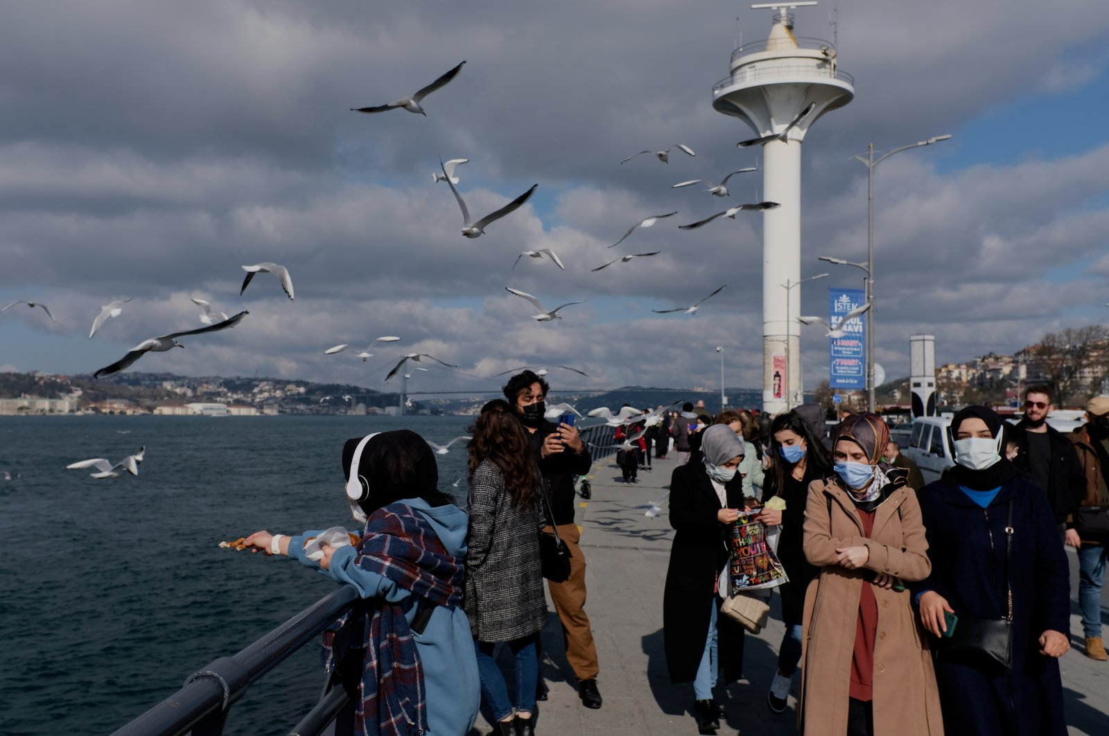 People wearing protective masks stroll by the Bosporus amid the COVID-19 outbreak in Istanbul, Turkey, Feb. 25, 2021. (Reuters Photo)