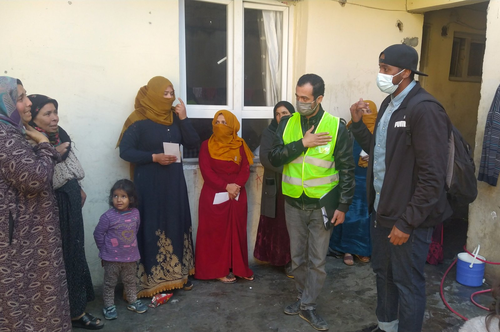Taha Saleh (R) talks to Syrian refugees during a visit to their home, in Şanlıurfa, southeastern Turkey, Feb. 28, 2021. (İHA PHOTO)