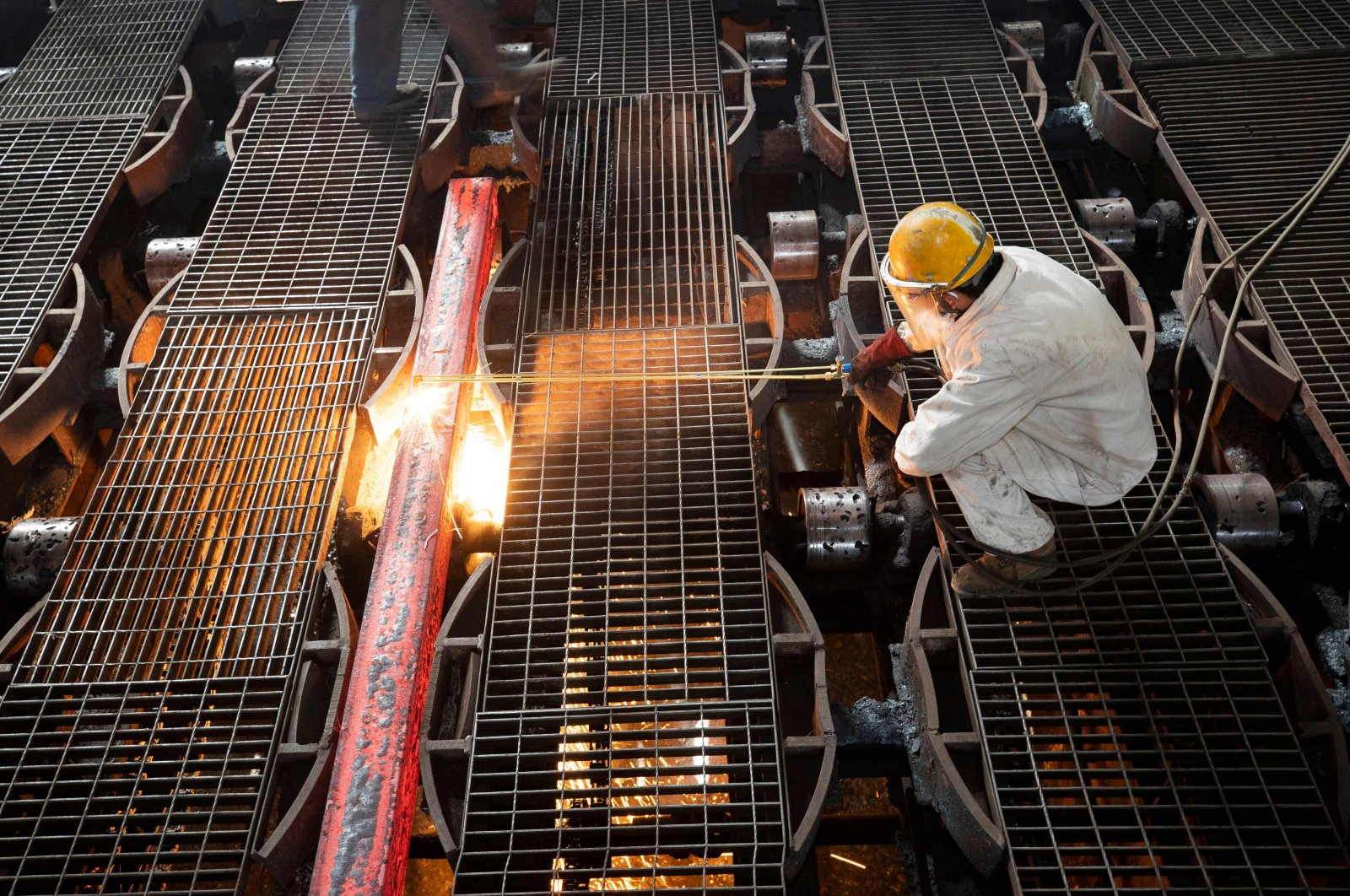 A worker makes an iron bar at a steel factory on the first day of the Lunar New Year, in Lianyungang, Jiangsu province, eastern China, on Feb. 12, 2021. (AFP Photo)