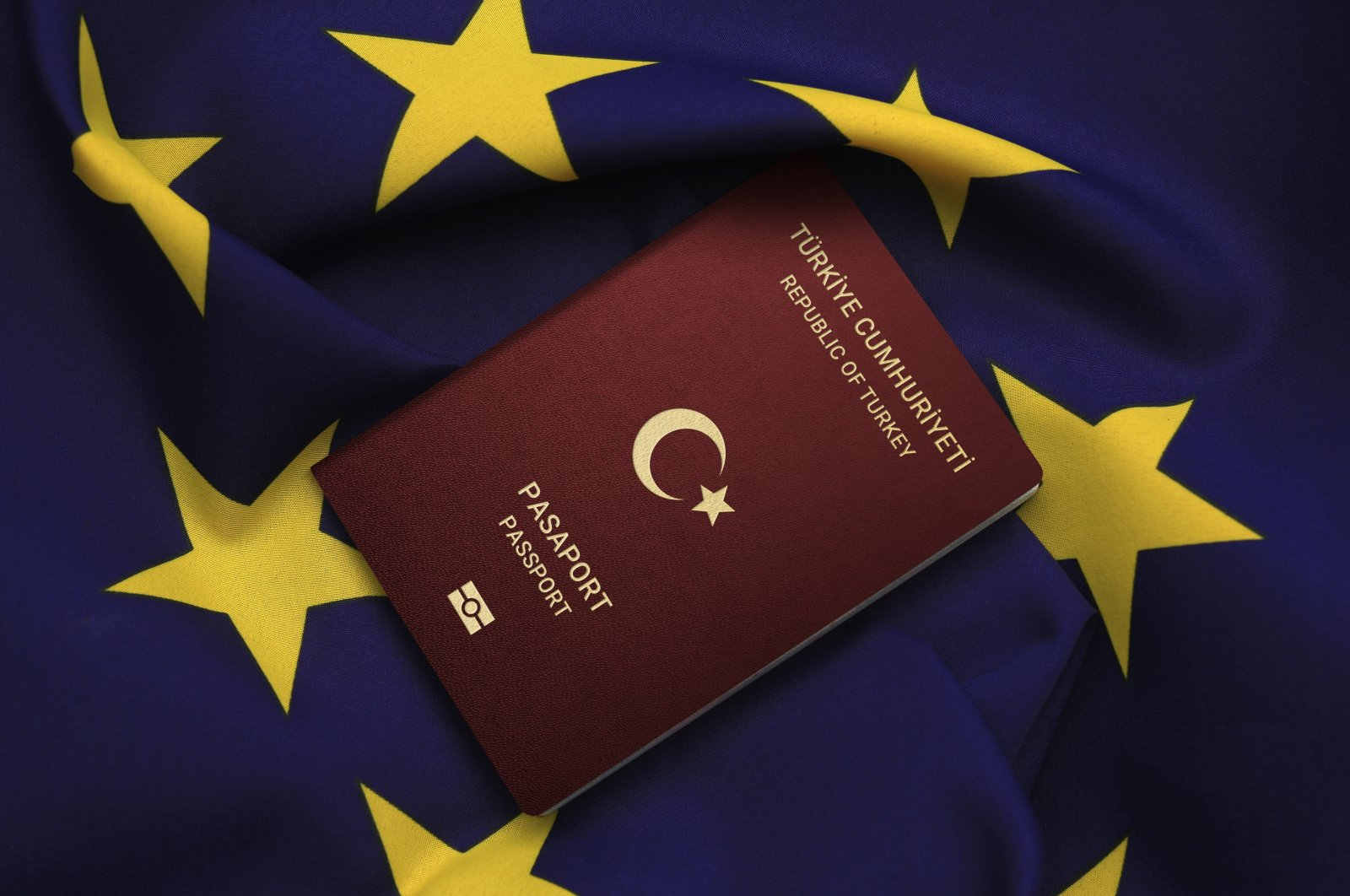 In this illustration, a Turkish passport is seen on the flag of the European Union. (Photo by Shutterstock)