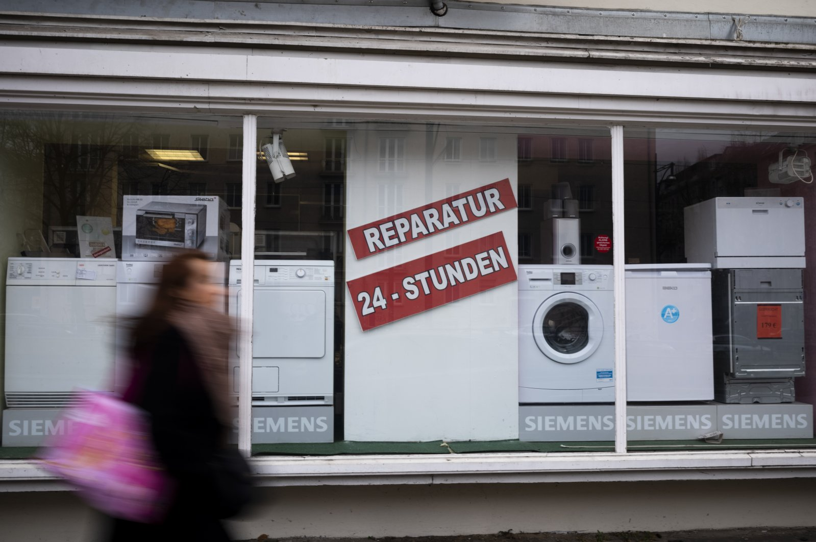 A person walks past a shop offering the repair of electronic equipment and domestic appliances in Berlin, Germany, Feb. 26, 2021. (AP Photo)