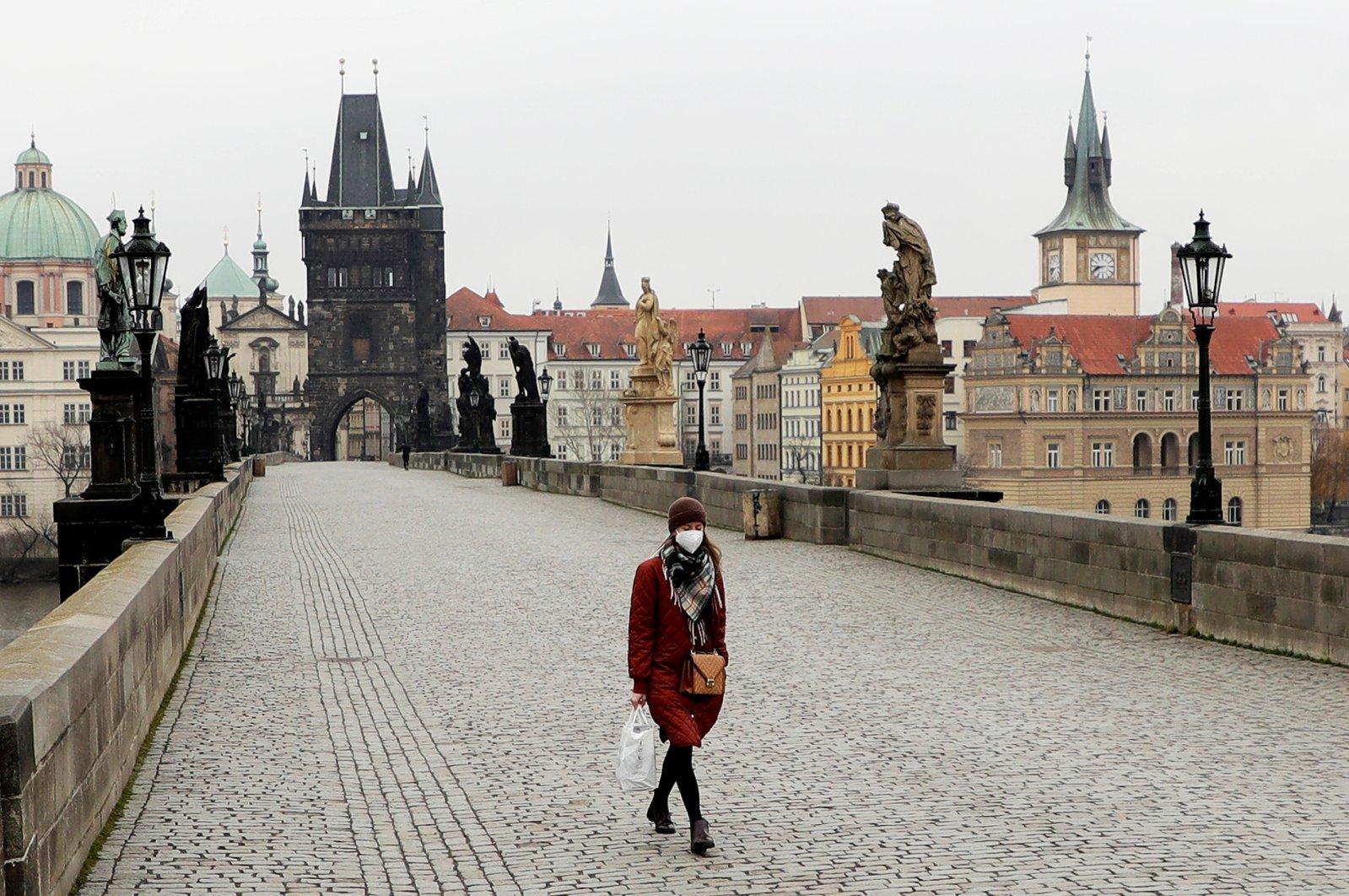 A woman wearing a face mask walks across the empty Charles Bridge in Prague, Czech Republic, March 1, 2021. (Reuters Photo)