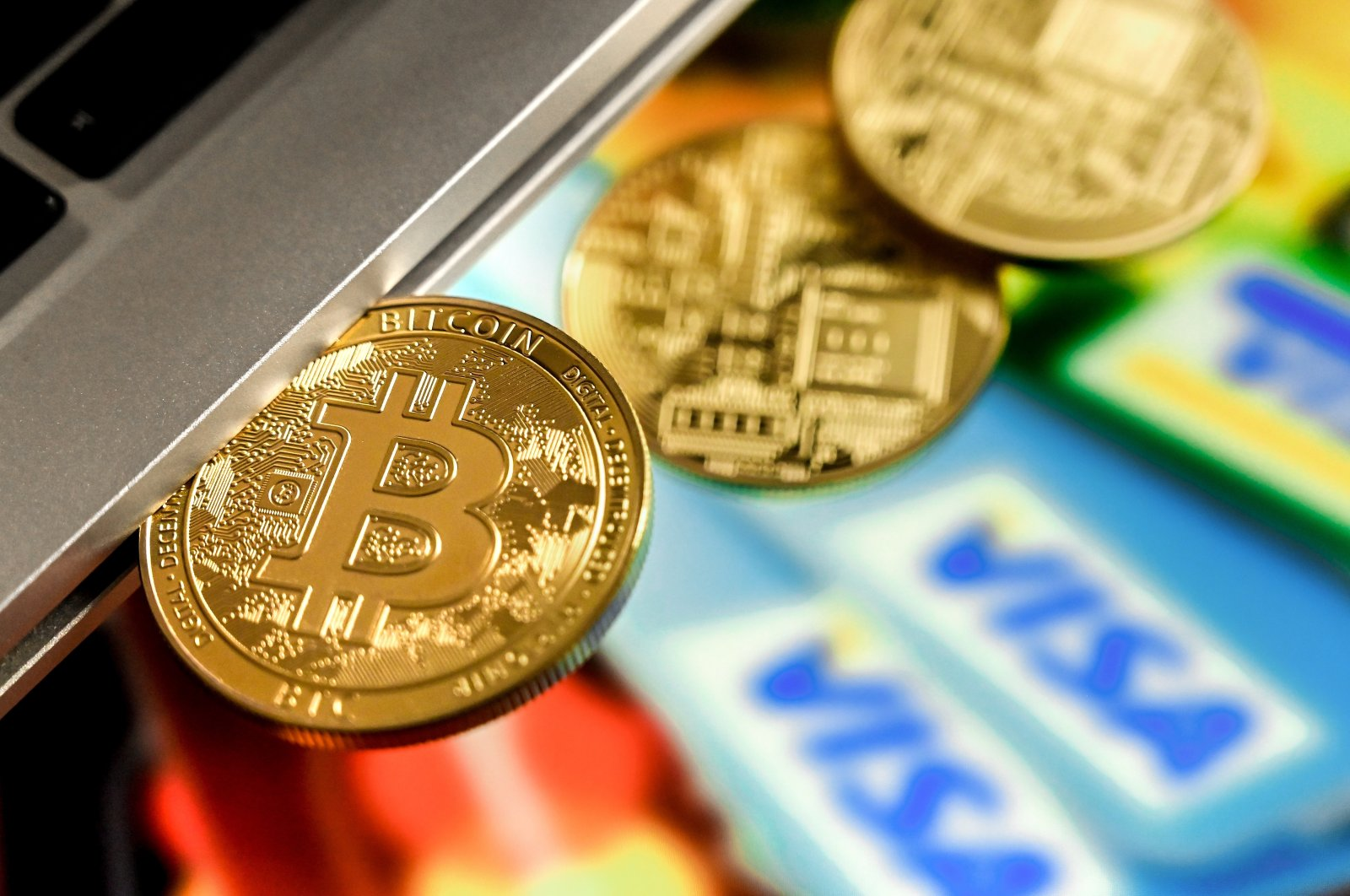 A bitcoin sits in a laptop's CD drive above several credit cards, in Duesseldorf, Germany, Feb. 17, 2021. (EPA Photo)