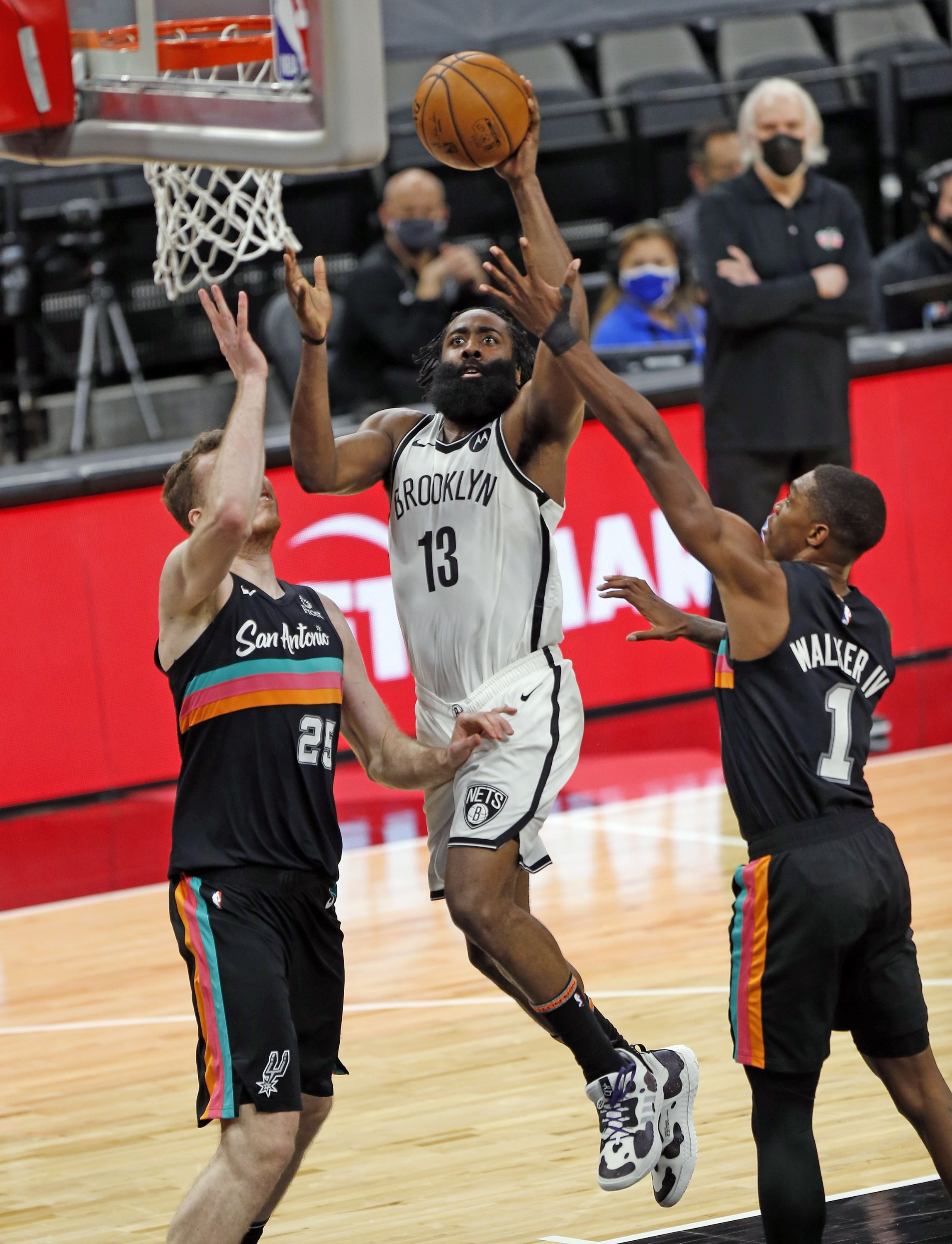 Brooklyn Nets' James Harden (C) drives to the basket against San Antonio Spurs' Lonnie Walker (R) in an NBA game at AT&T Center, in San Antonio, Texas, March 1, 2021. (AFP Photo)