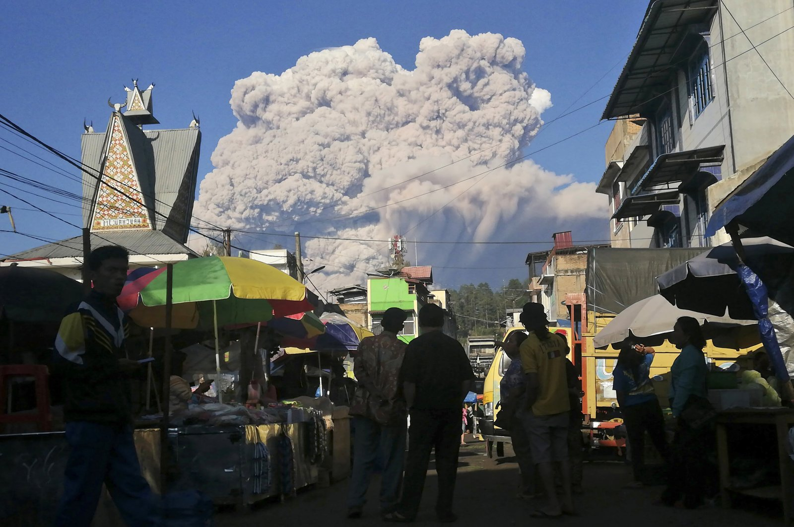 People watch as Mount Sinabung spews volcanic material during an eruption, at a market in Karo, North Sumatra, Indonesia, Tuesday, March 2, 2021. (AP Photo)