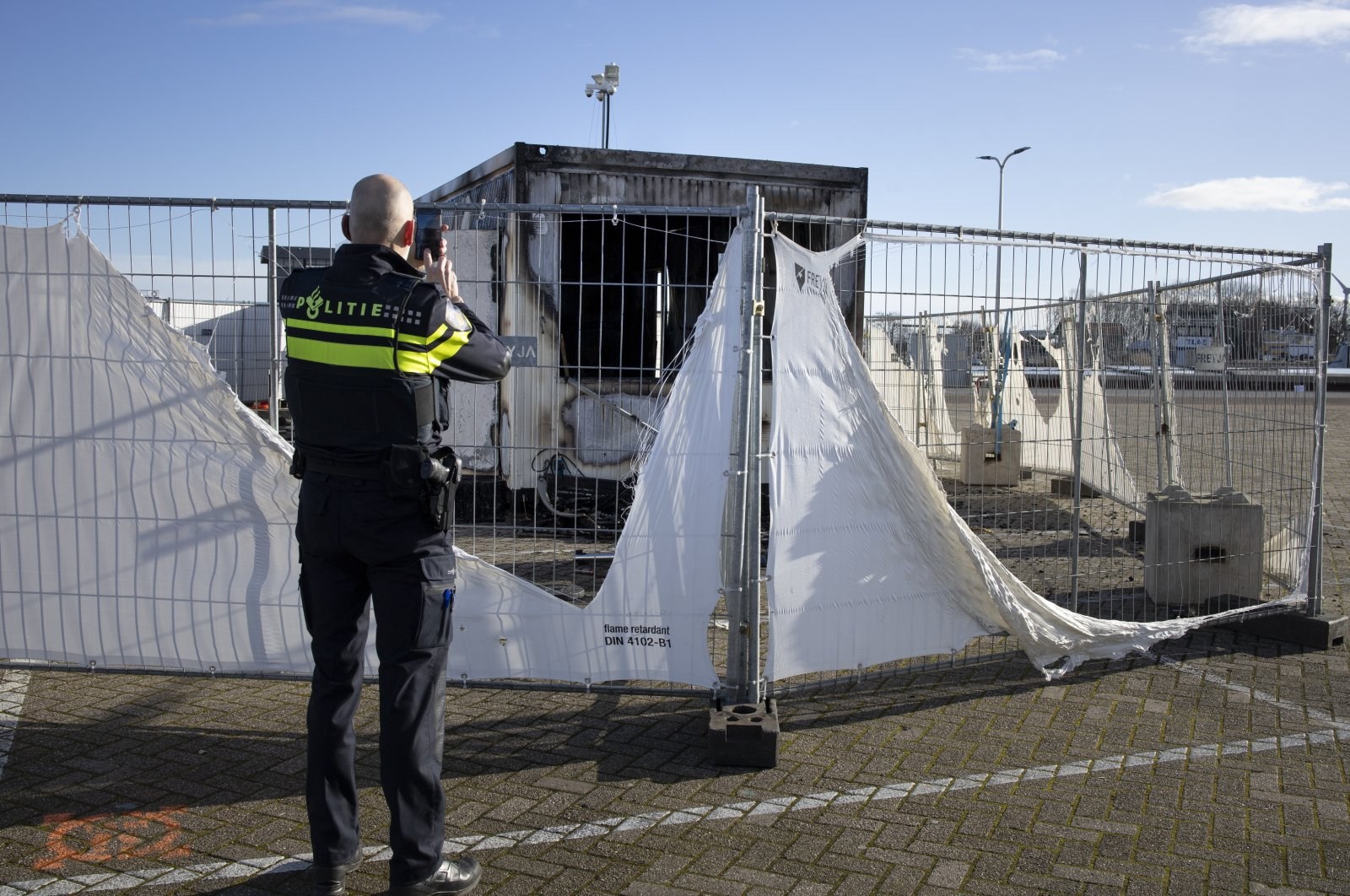 A police officer takes pictures of a destroyed COVID-19 testing facility in the fishing village of Urk in the Netherlands after it was set on fire the night before by rioting youths protesting on the first night of a nationwide curfew, Jan. 24, 2021. (AP Photo)