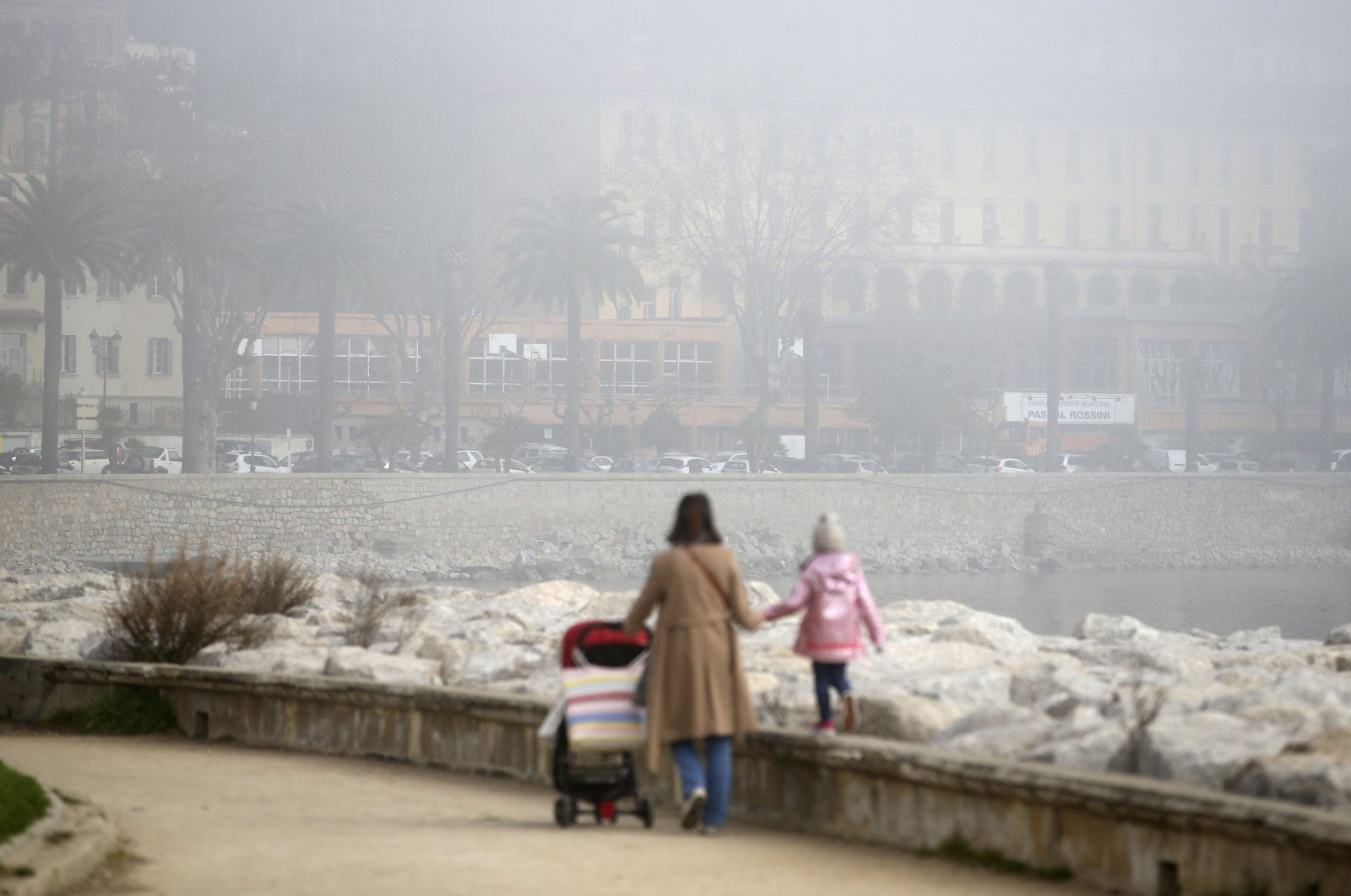 A woman walks with her child at the Miot square as heavy smog and pollution envelopes the capital Ajaccio on the French Mediterranean island of Corsica on Feb. 25, 2021. (AFP Photo)