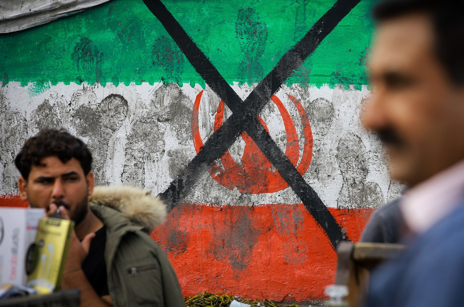 Protestors pass by a defaced painting of the Iranian flag during a rally against the breach of Iraqi sovereignty by the U.S.and Iran, Baghdad, Iraq, Jan. 10, 2020.  (Photo by Getty Images)