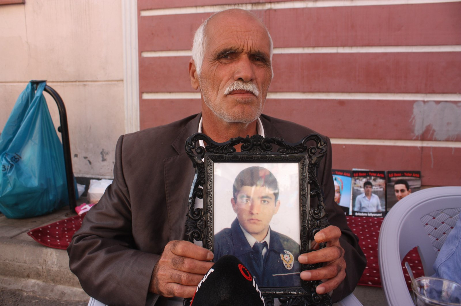 Şehmus Kaya holds a picture of his son Vedat during a sit-in protest against the PKK in southeastern Diyarbakır province, Turkey, Oct. 22, 2019. (İHA Photo)