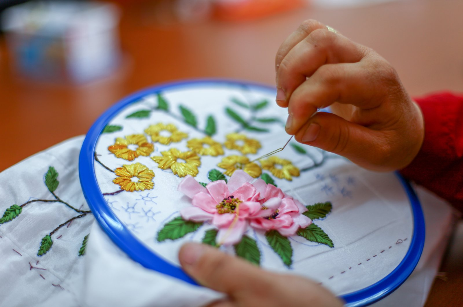 A woman applies Turkish embroidery detailing a floral motif on a piece of fabric. (Shutterstock Photo)