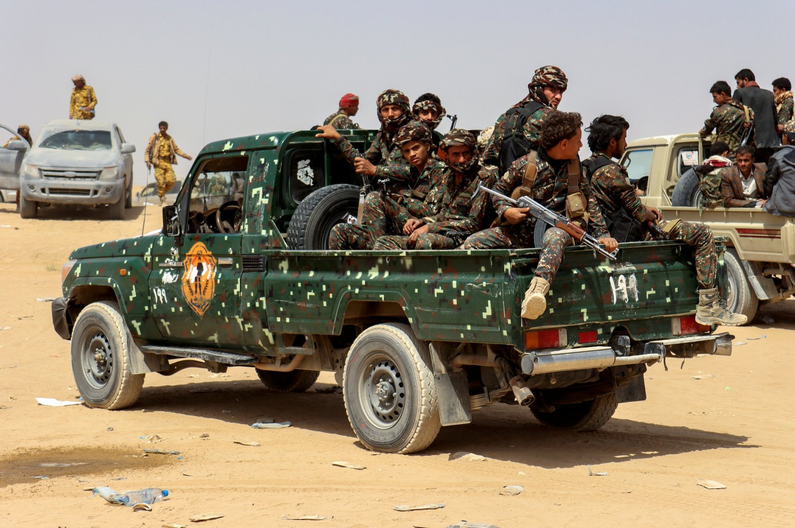Soldiers ride on the back of a patrol truck during the burial of Brig. Gen. Abdul-Ghani Shaalan, commander of the Special Security Forces in Marib who was killed in recent fighting with Houthi fighters in Marib, Yemen Feb. 28, 2021. (Reuters Photo)