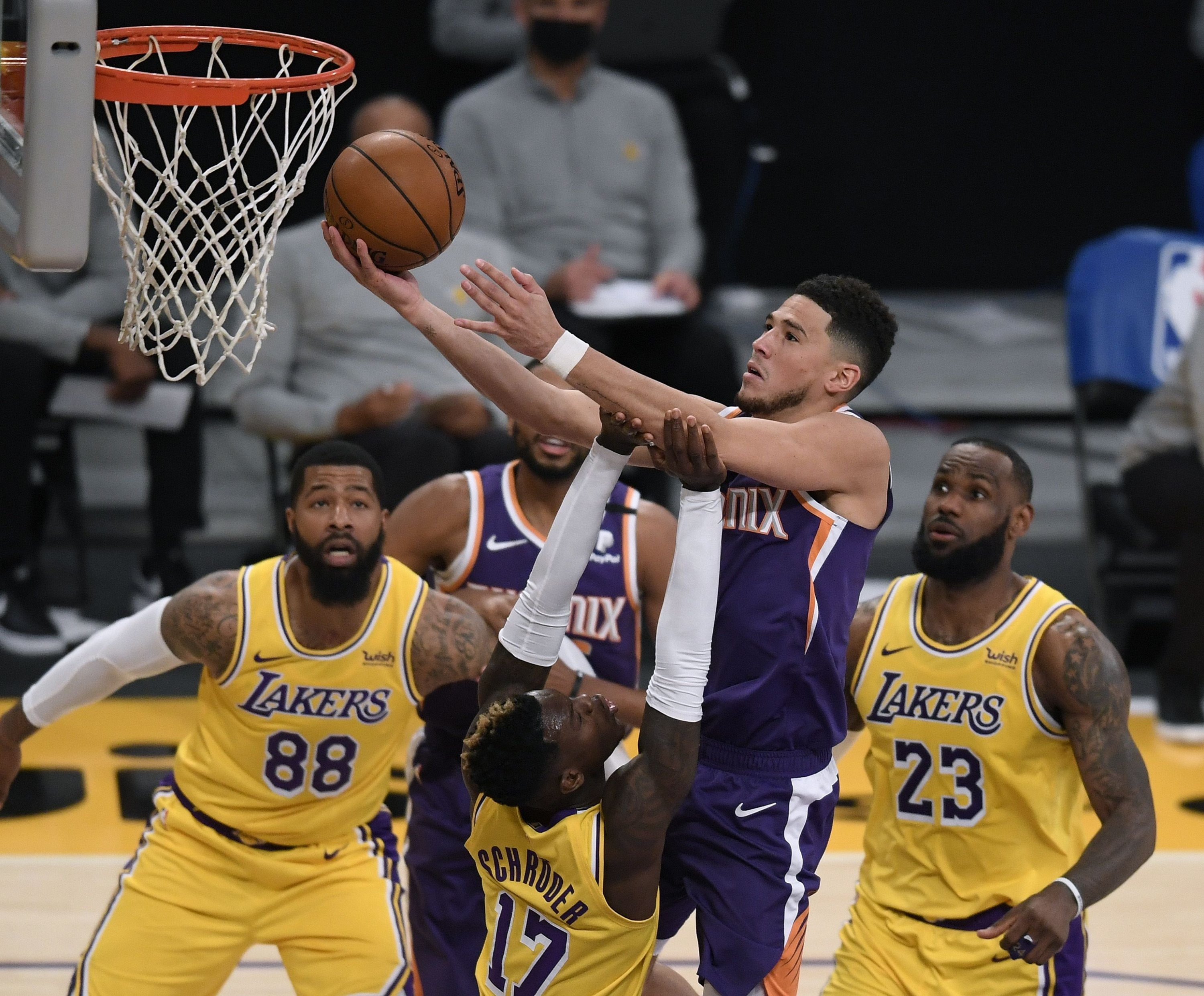 Phoenix Suns' Devin Booker (C) scores over Los Angeles Lakers' Dennis Schroder (L) as LeBron James (R) and Markieff Morris (2nd L) look on during an NBA match at Staples Center, Los Angeles, California, March 02, 2021. (AFP Photo)