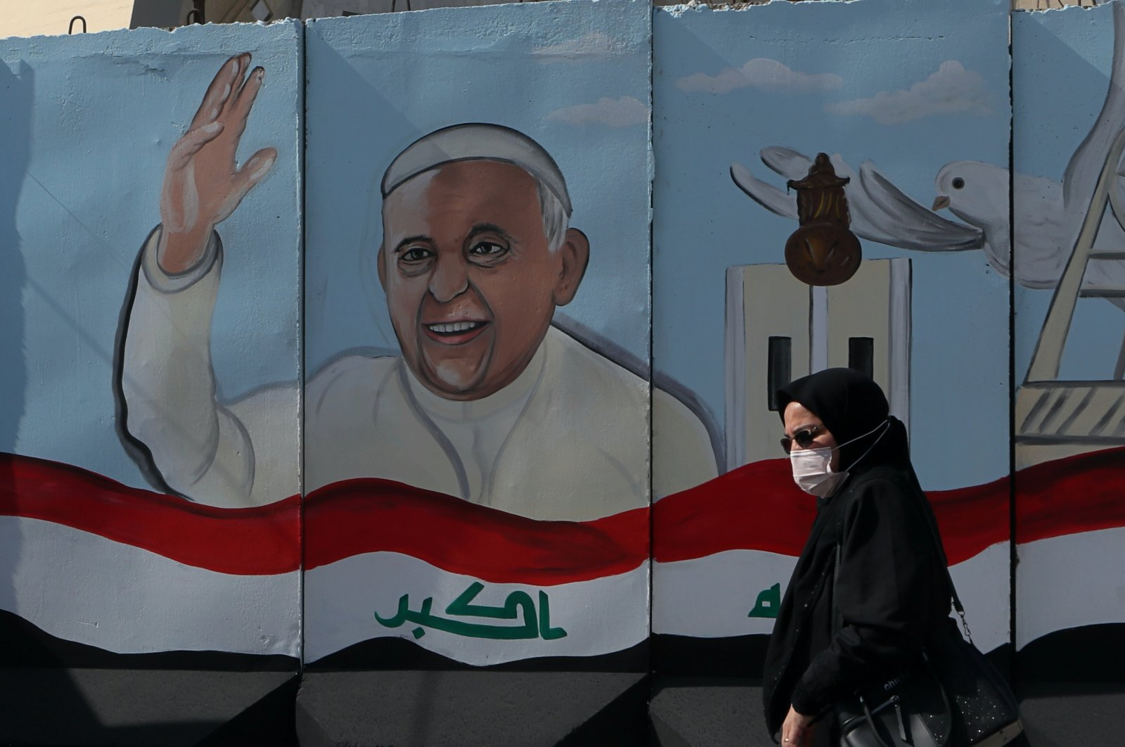 A woman walks past a mural depicting Pope Francis on a concrete wall placed by Iraqi security forces to surround the Our Lady of Salvation Church during preparations for the Pope's visit in Baghdad, Iraq, Monday, March 1, 2021. (AP Photo)