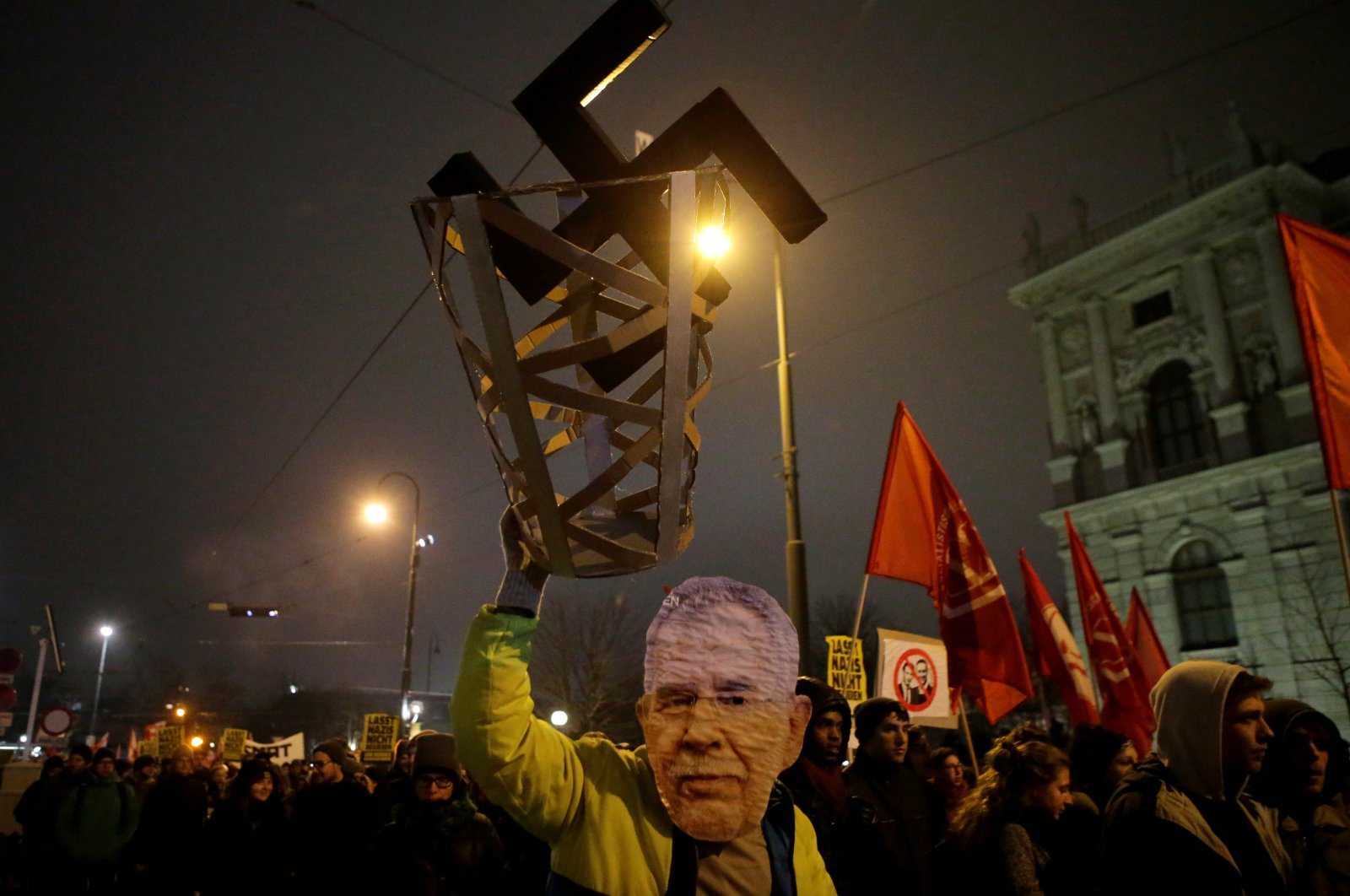 A protester wearing a President Alexander Van der Bellen mask holds a swastika in a basket during a demonstration against the far-right Freedom Party's annual Academics' Ball in Vienna, Austria, Jan. 26, 2018. (Reuters Photo)