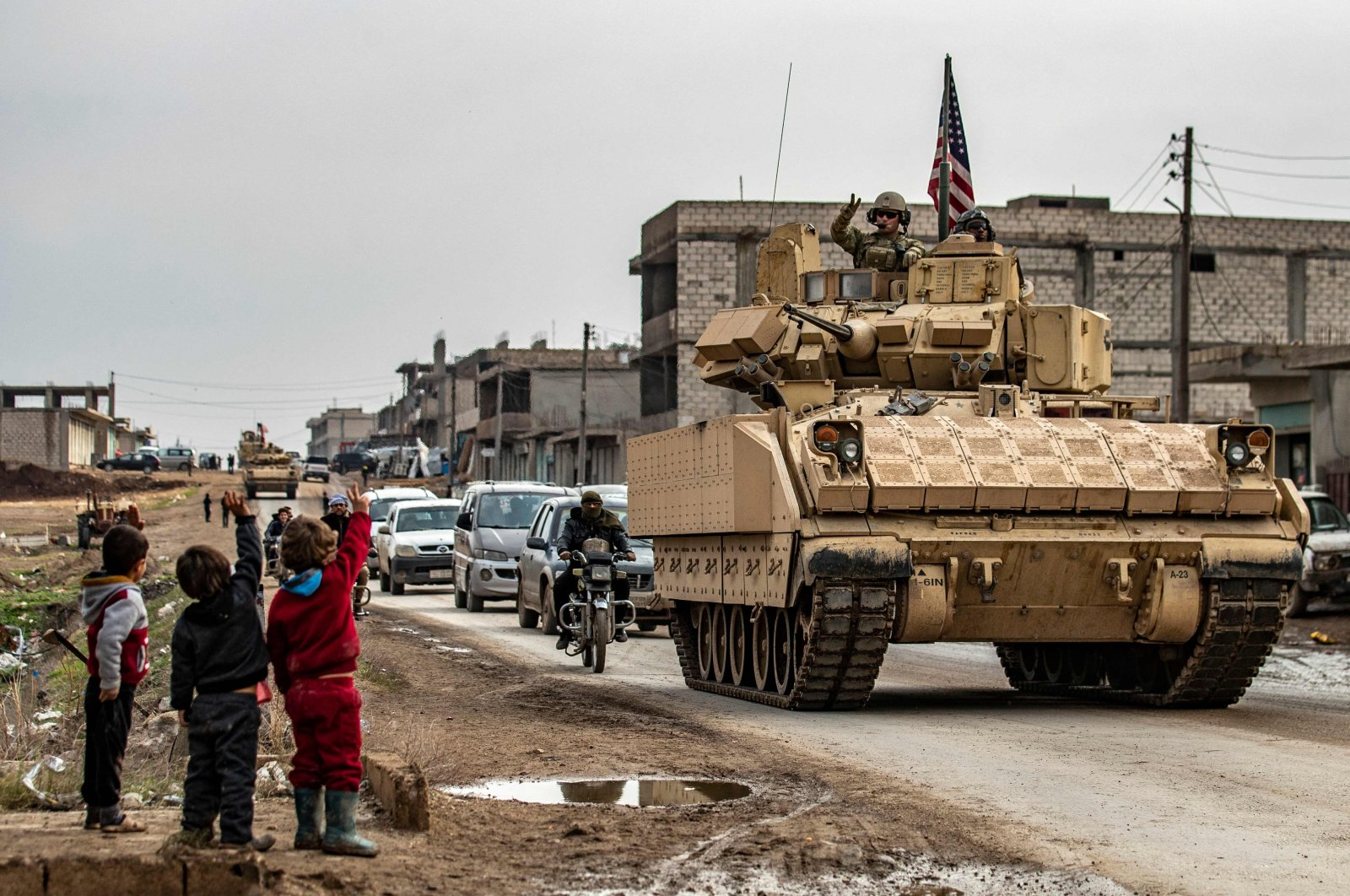 Children greet a U.S. soldier atop a Bradley Fighting Vehicle (BFV) as U.S. troops patrol in the Syrian town of al-Jawadiyah in the northeastern Hassakeh province, Dec. 17, 2020. (AFP Photo)
