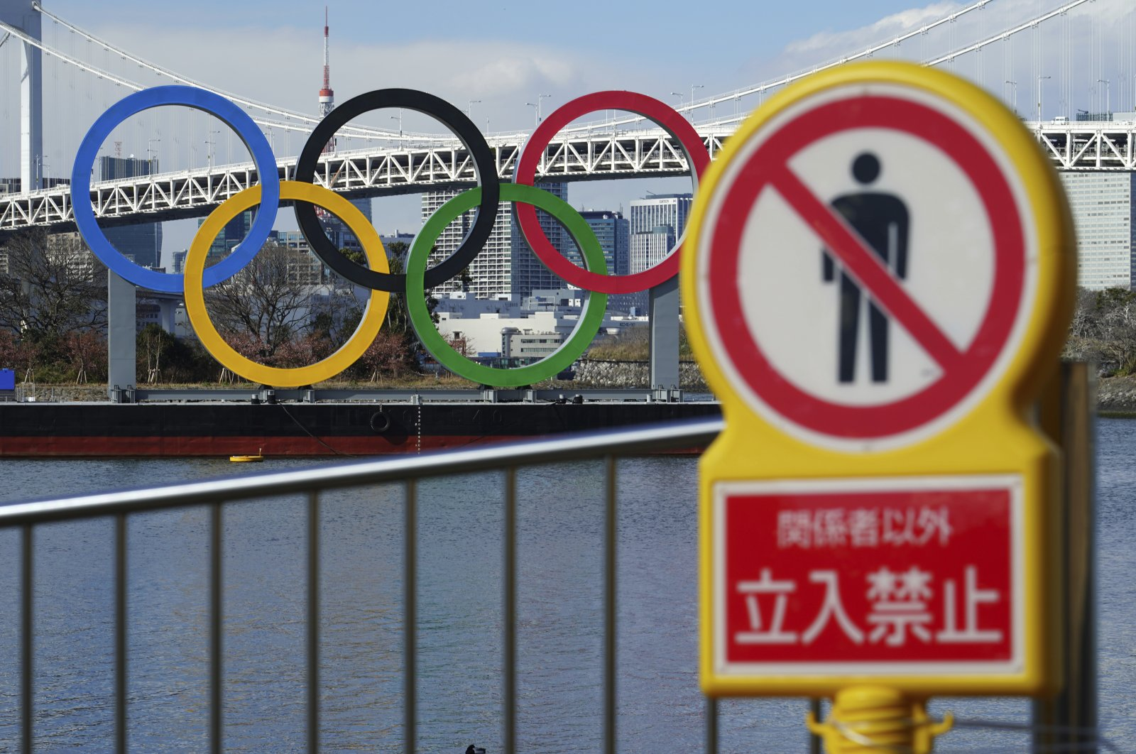 "The Olympic rings floating in the water seen near a sign ""No Trespassing"" in the Odaiba section, Tokyo, Japan, Feb. 18, 2021. (AP Photo)"