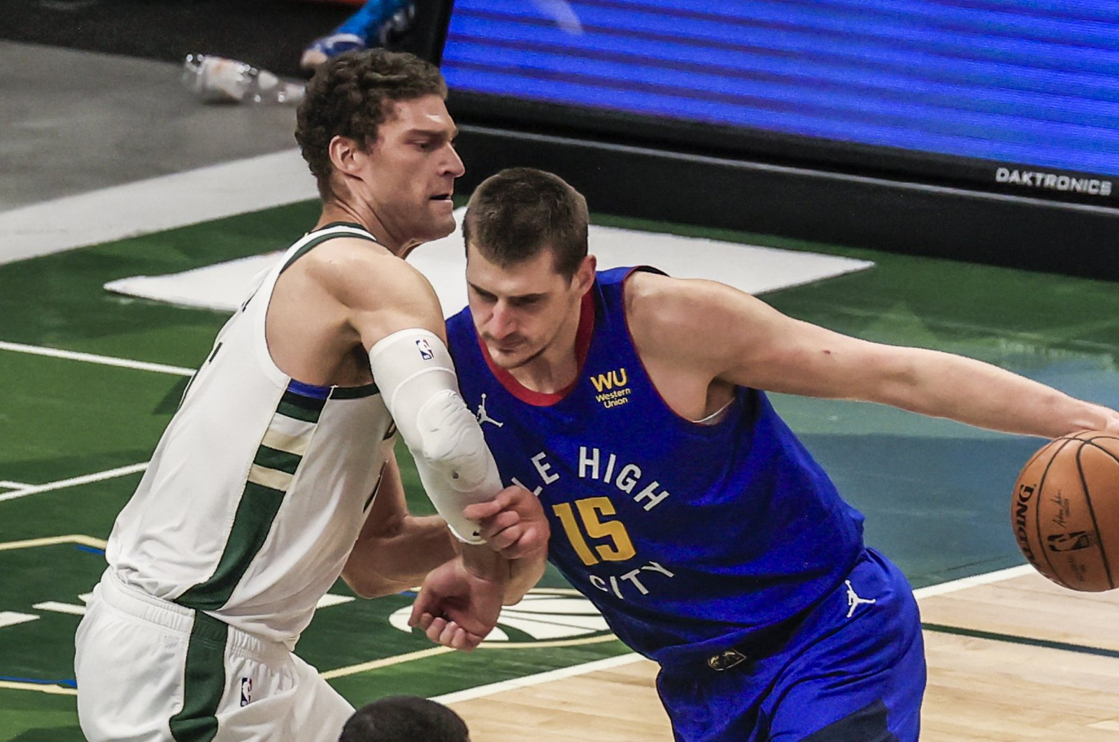 Denver Nuggets' Nikola Jokic (R) drives on Milwaukee Bucks' Brook Lopez (L) in an NBA game, Milwaukee, Wisconsin, March 2, 2021. (EPA Photo)