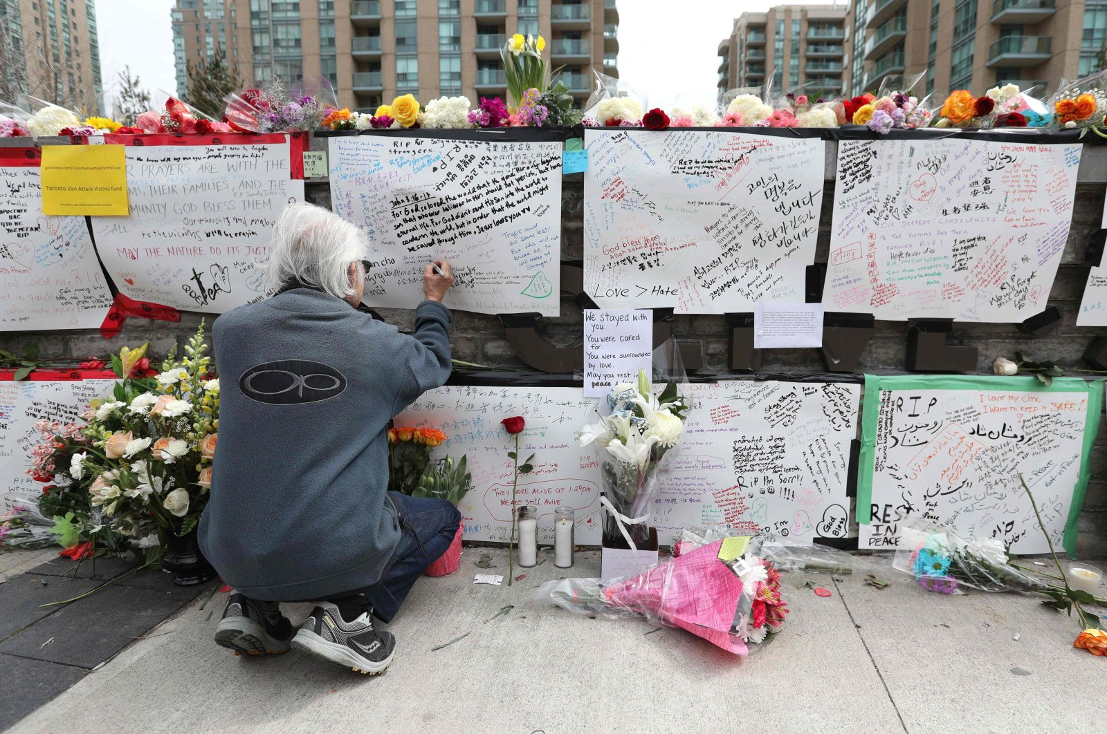 Jack Young leaves a note on April 24, 2018, at a makeshift memorial for victims in the van attack in Toronto, Ontario. (AFP Photo)