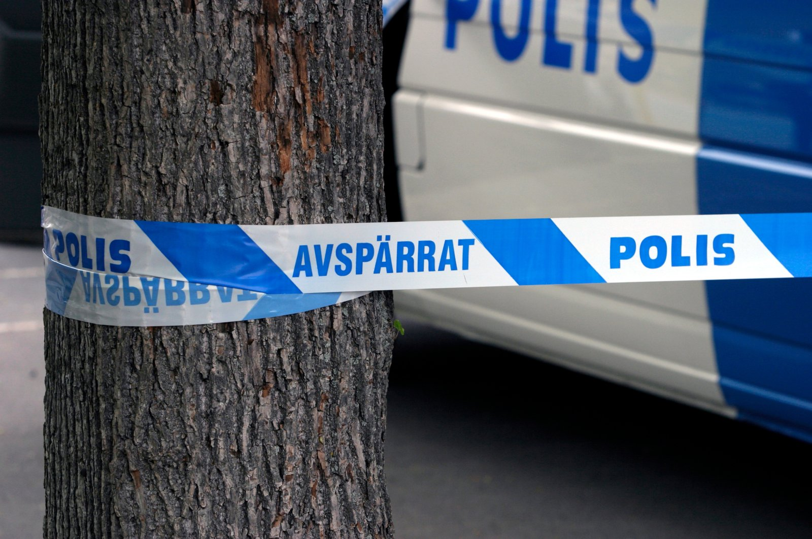 """A Swedish police barricade and a police vehicle are seen in the background at a crime scene in Sweden with the sign reading """"Restricted, police."""" (Shutterstock Photo)"""