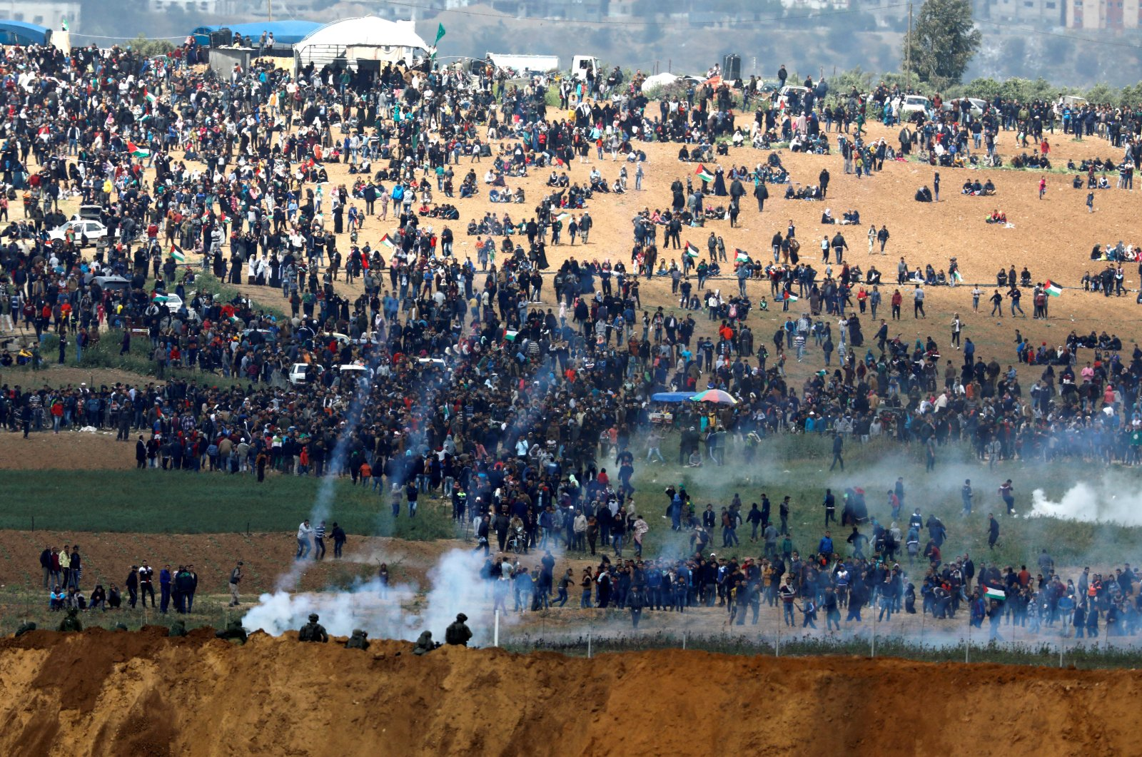 Israeli soldiers shoot tear gas from the Israeli side of the Israel-Gaza border, as Palestinians protest on the Gaza side of the border, March 30, 2018. (Reuters File Photo)