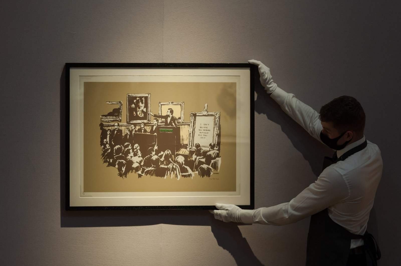 """A staff member poses with """"Morons (Sepia)"""" screenprint in colors, 2007, by Banksy during a press preview at Christie's in London, England, on Sept. 09, 2020. (Photo by WIktor Szymanowicz/NurPhoto via Getty Images)"""