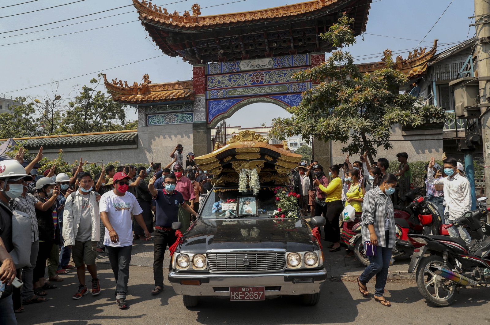 Bystanders flash a three-fingered sign of resistance as the body of Kyal Sin is driven out from a Yunnan Chinese temple in Mandalay, Myanmar, March 4, 2021. (AP Photo)