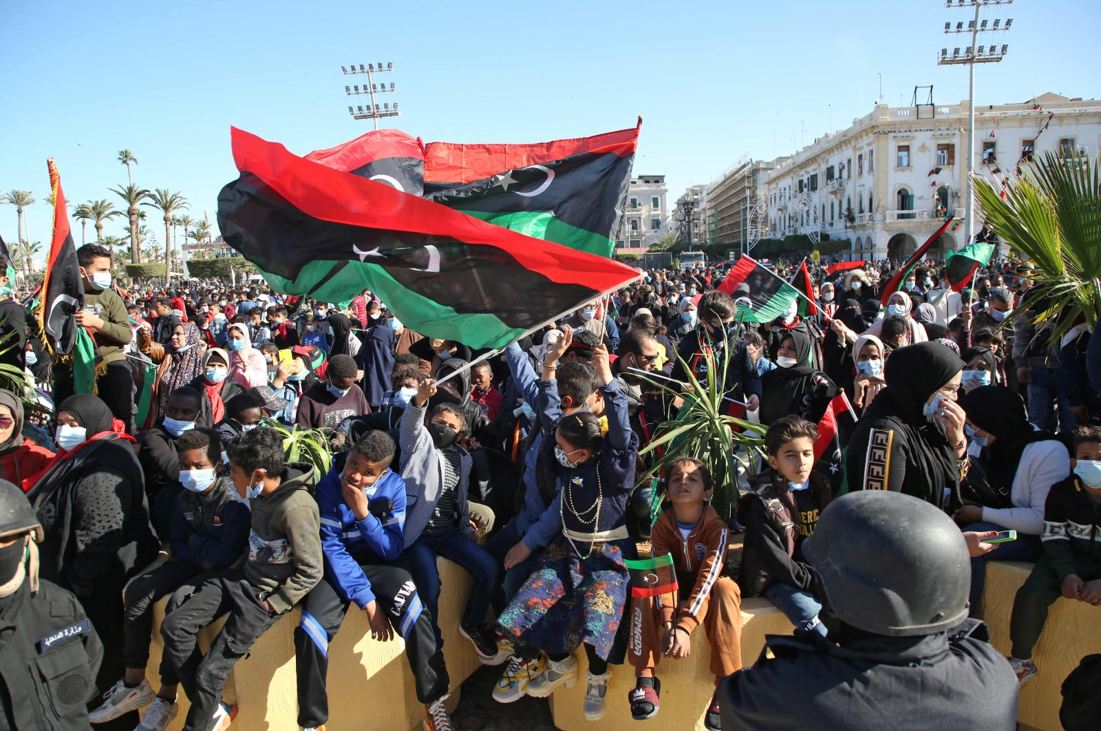 Libyans wave national flags as they gather to celebrate the 10th anniversary of the 2011 revolution in Martyr's Square, Tripoli, Libya, Feb. 17, 2021. (AFP Photo)