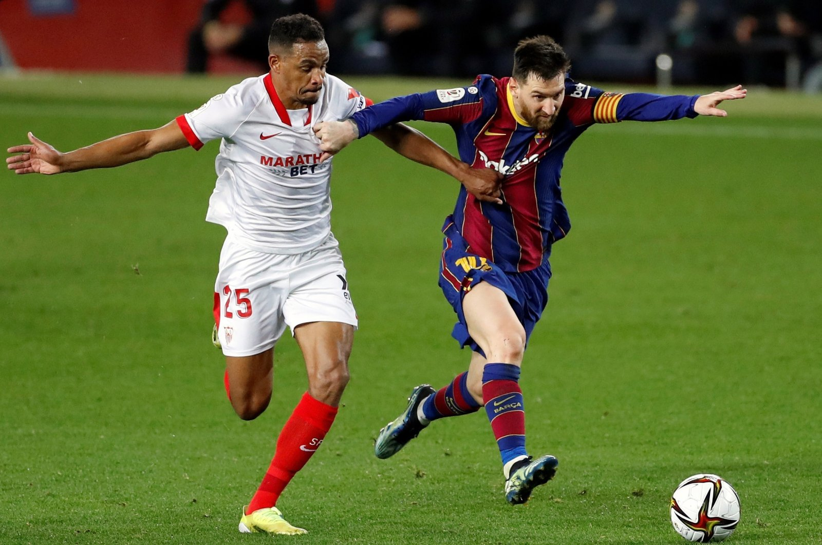 Barcelona's Lionel Messi (R) vies for the ball with Sevilla midfielder Fernando Reges (L) during the second leg Copa Del Rey semifinal at Camp Nou, Barcelona, Spain, March 3, 2021. (EPA Photo)