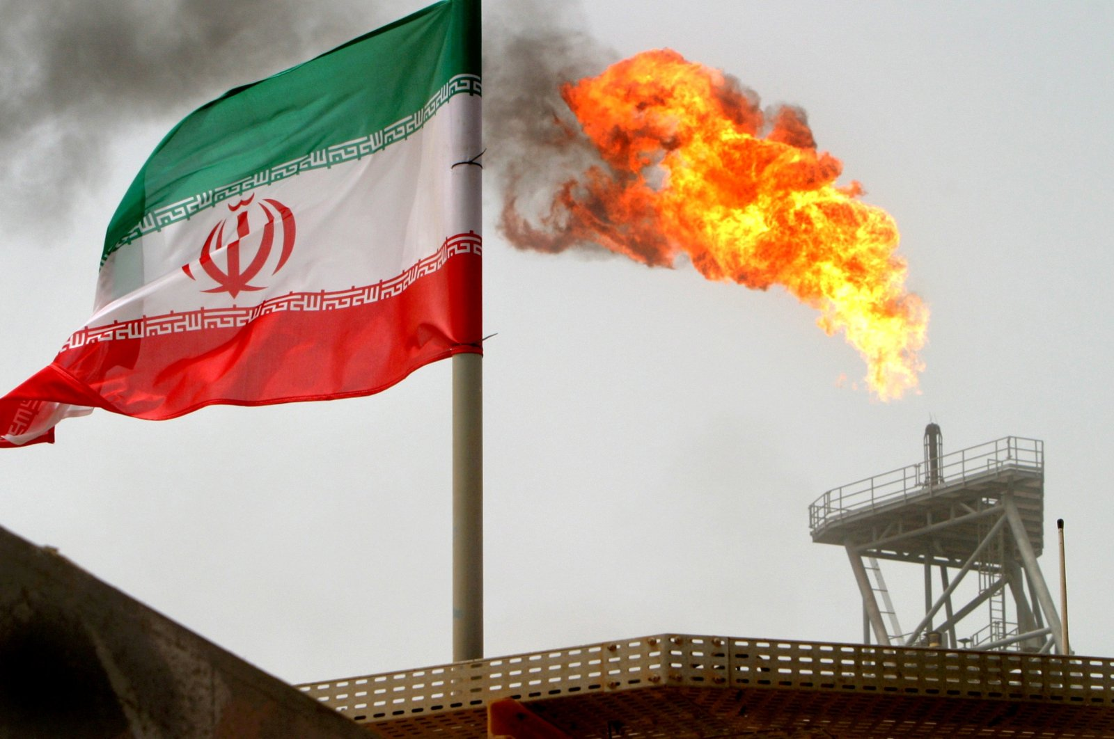 A gas flare at an oil production platform in the Soroush oil fields is seen alongside an Iranian flag in the Persian Gulf, Iran, July 25, 2005. (Reuters Photo)