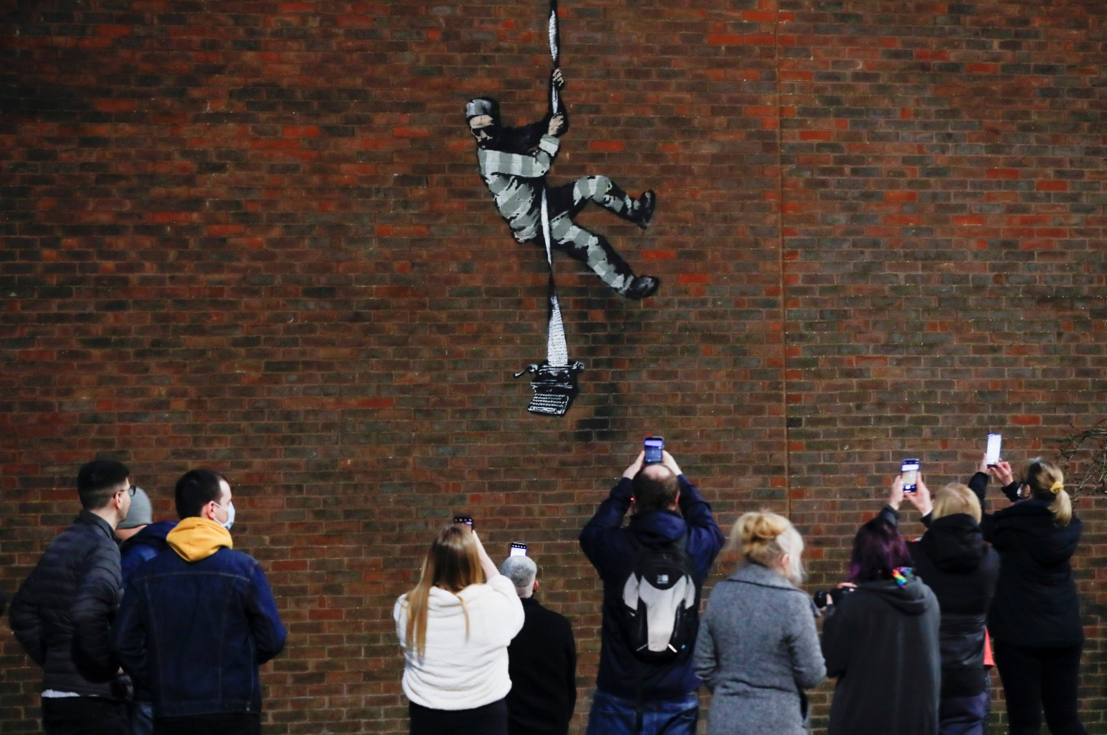 People take pictures of a mural by street artist Banksy on a wall at HM Reading Prison in Reading, Britain, March 1, 2021. (REUTERS)