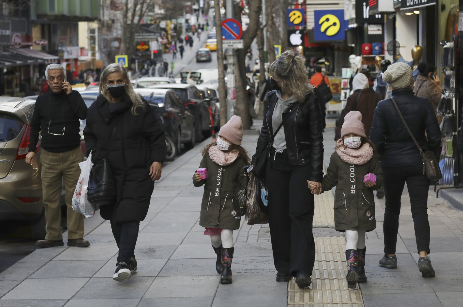 People with face masks walk along a busy street in Ankara, Turkey, March 2, 2021. (AP Photo)