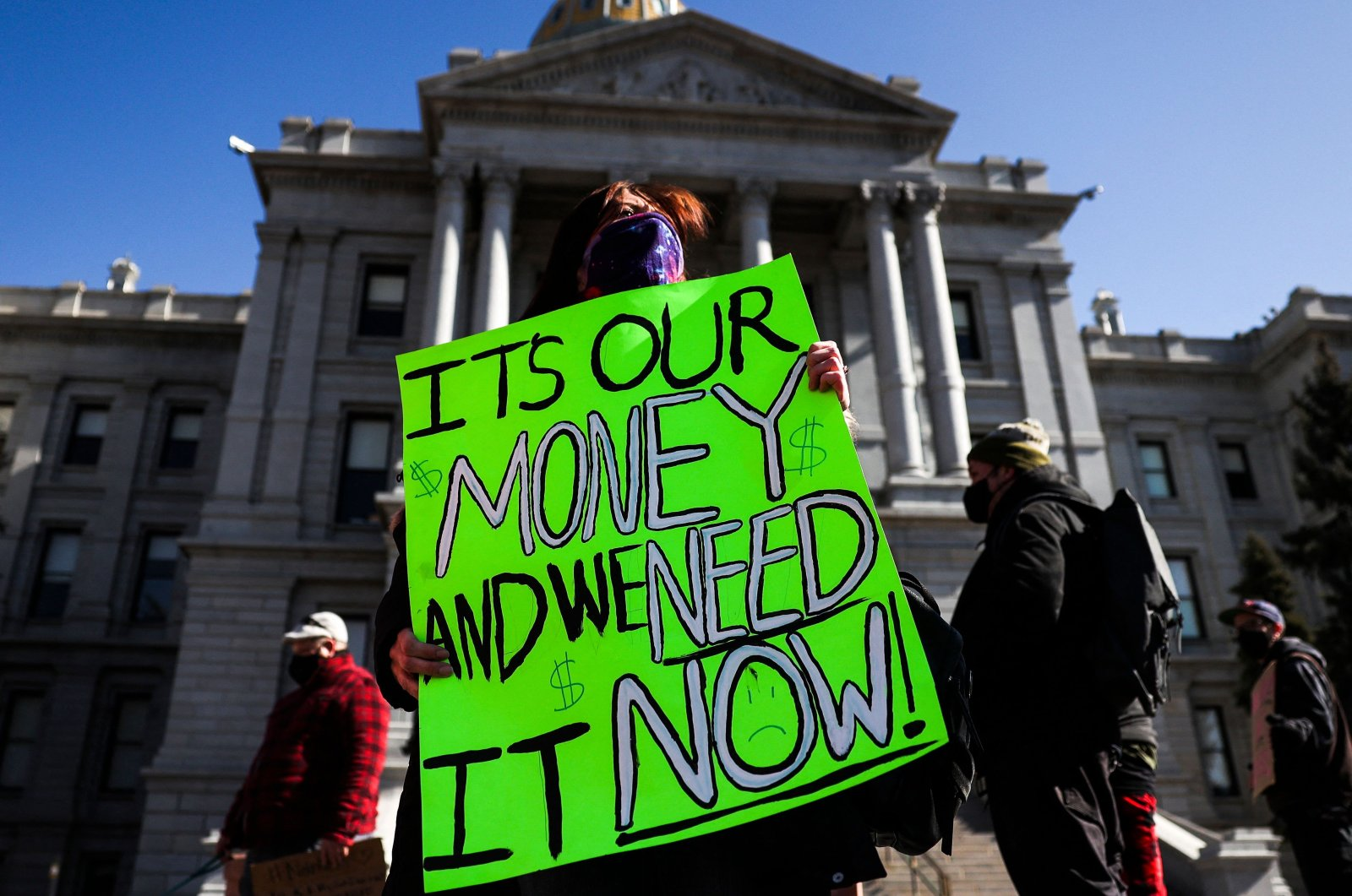 Monica Walsh holds a sign outside the Colorado State Capitol during a demonstration demanding answers about a lack of financial relief from the state in Denver, Colorado, Feb. 8, 2021. (AFP Photo)