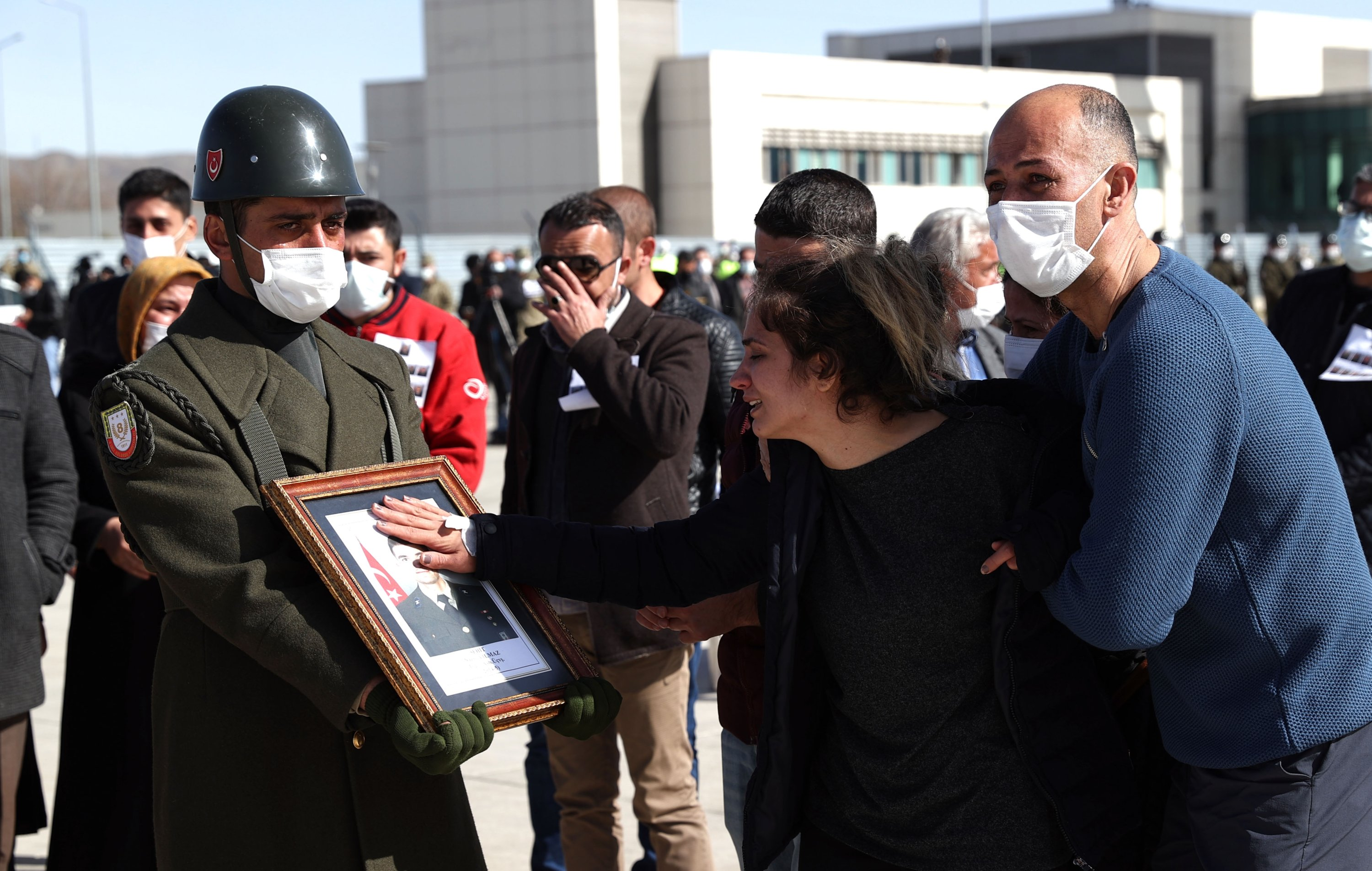A relative of one of the victims touches his photo carried by a honor guard during the military funeral, in Elazığ, eastern Turkey, March 5, 2021. (AA PHOTO)