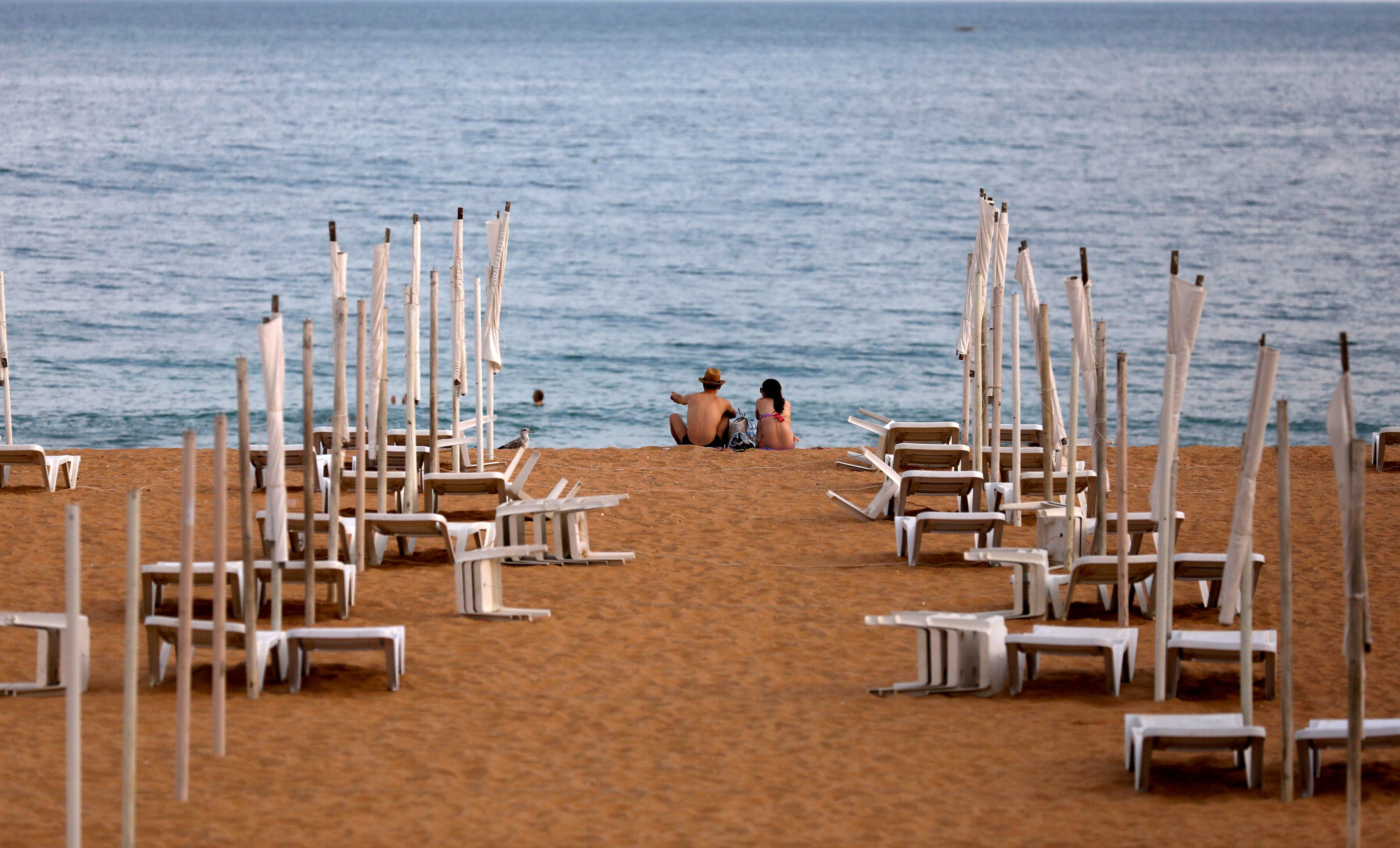 A couple next to rows of empty hammocks during the coronavirus pandemic in Albufeira, Portugal, July 20, 2020. (REUTERS/Rafael Marchante/File Photo/File Photo)