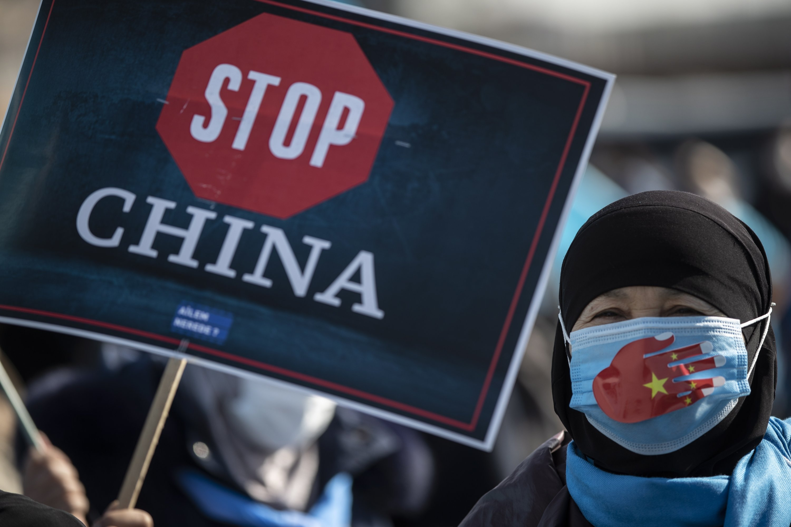 Uyghur protestors who have not heard from their families living in Xinjiang hold placards and the Uyghur flag during a protest against China, in Istanbul, Turkey, Feb. 26, 2021. (EPA Photo)