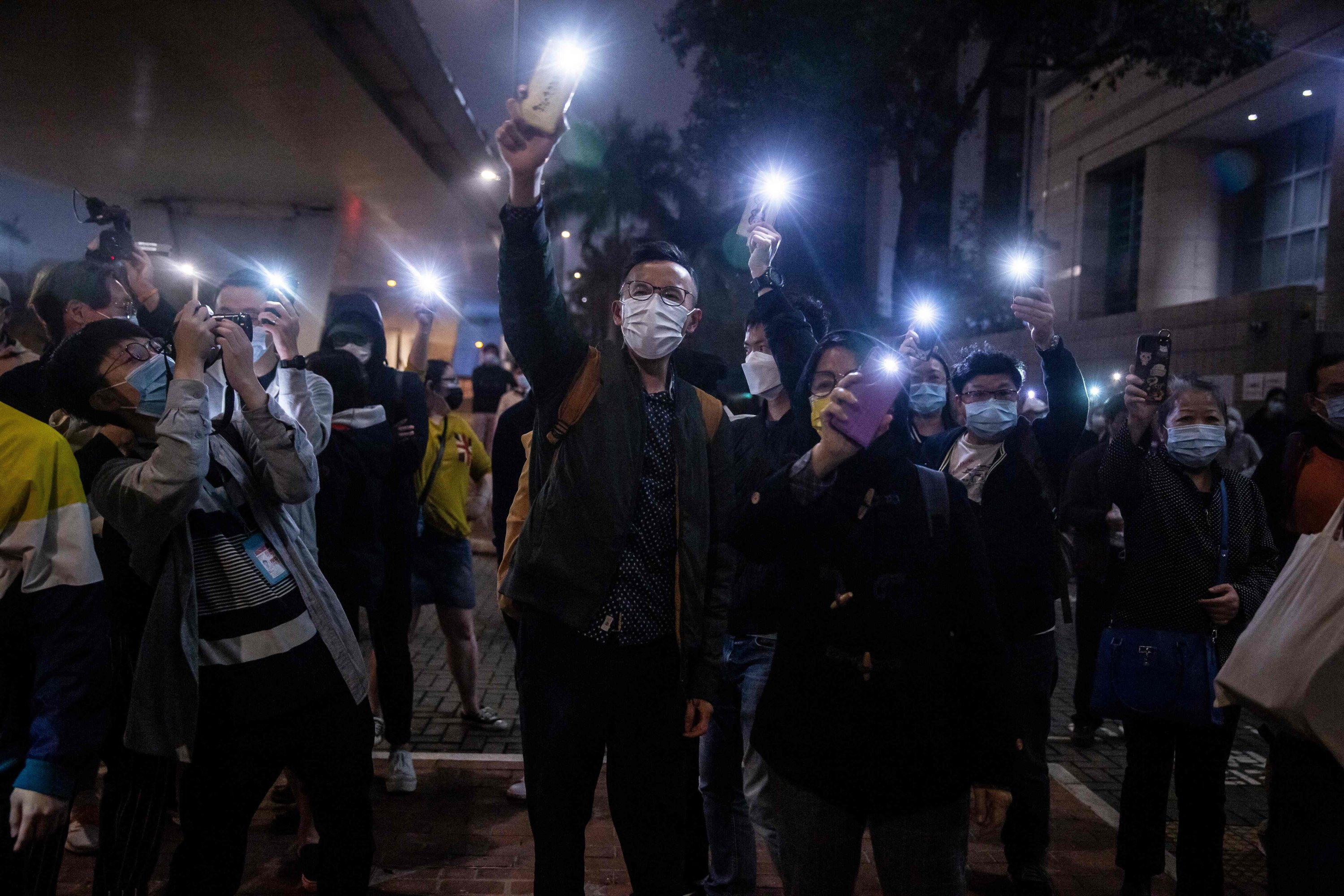 Supporters hold up their phones with the torch on after four anti-Beijing activists charged for conspiracy to commit subversion were released on bail, outside West Kowloon court in Hong Kong on March 5, 2021. (AFP Photo)