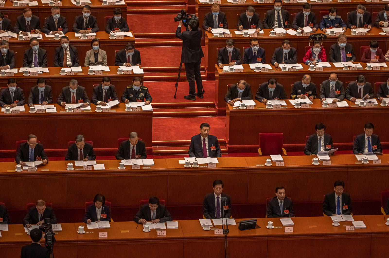 Chinese President Xi Jinping (C) with other delegates listen to a speech by Premier Li Keqiang (not pictured) during the opening session of the National People's Congress (NPC) at the Great Hall of the People, in Beijing, China, March 5, 2021.(EPA-EFE Photo)