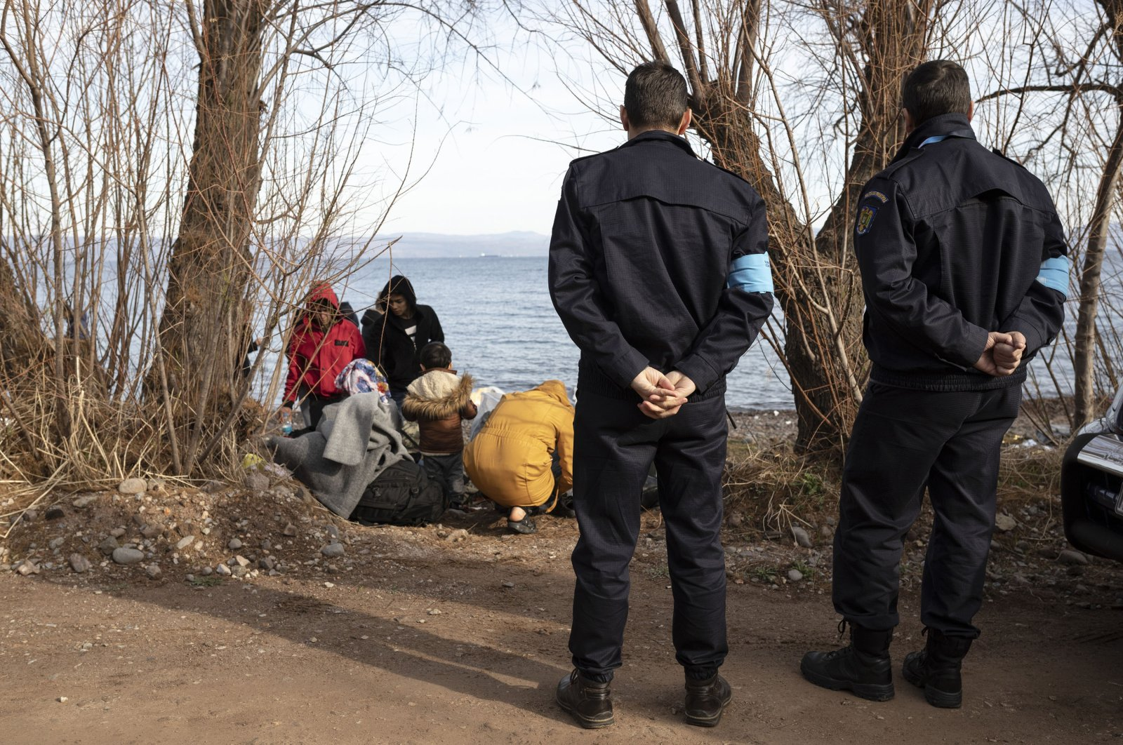 Frontex border officers stand by migrants from Afghanistan on the shore near the village of Skala Sikamineas on the island of Lesbos, Greece, March 1, 2020. (Photo by Getty Images)