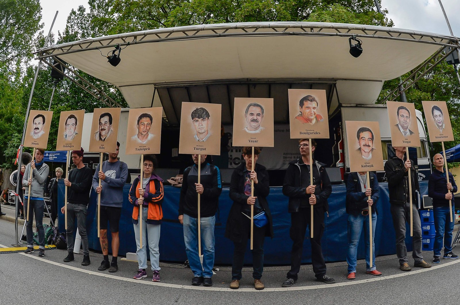 Protestors hold up signs with pictures of the victims of the neo-Nazi cell National Socialist Underground (NSU), in Munich, Germany, July 11, 2018. (AFP)