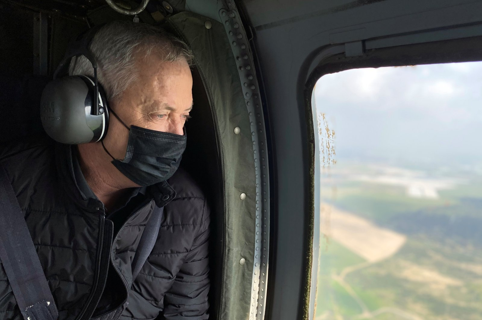Israeli Defence Minister Benny Gantz wears a face mask as he looks out from the window of a helicopter during a tour of the Gaza border area, southern Israel, March 2, 2021. (Reuters Photo)