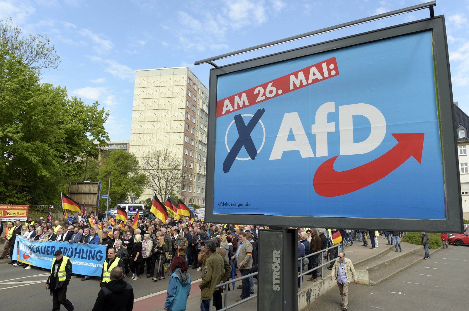 AfD supporters walk along a party elections poster in Erfurt, Germany, May 1, 2019. (AP Photo)