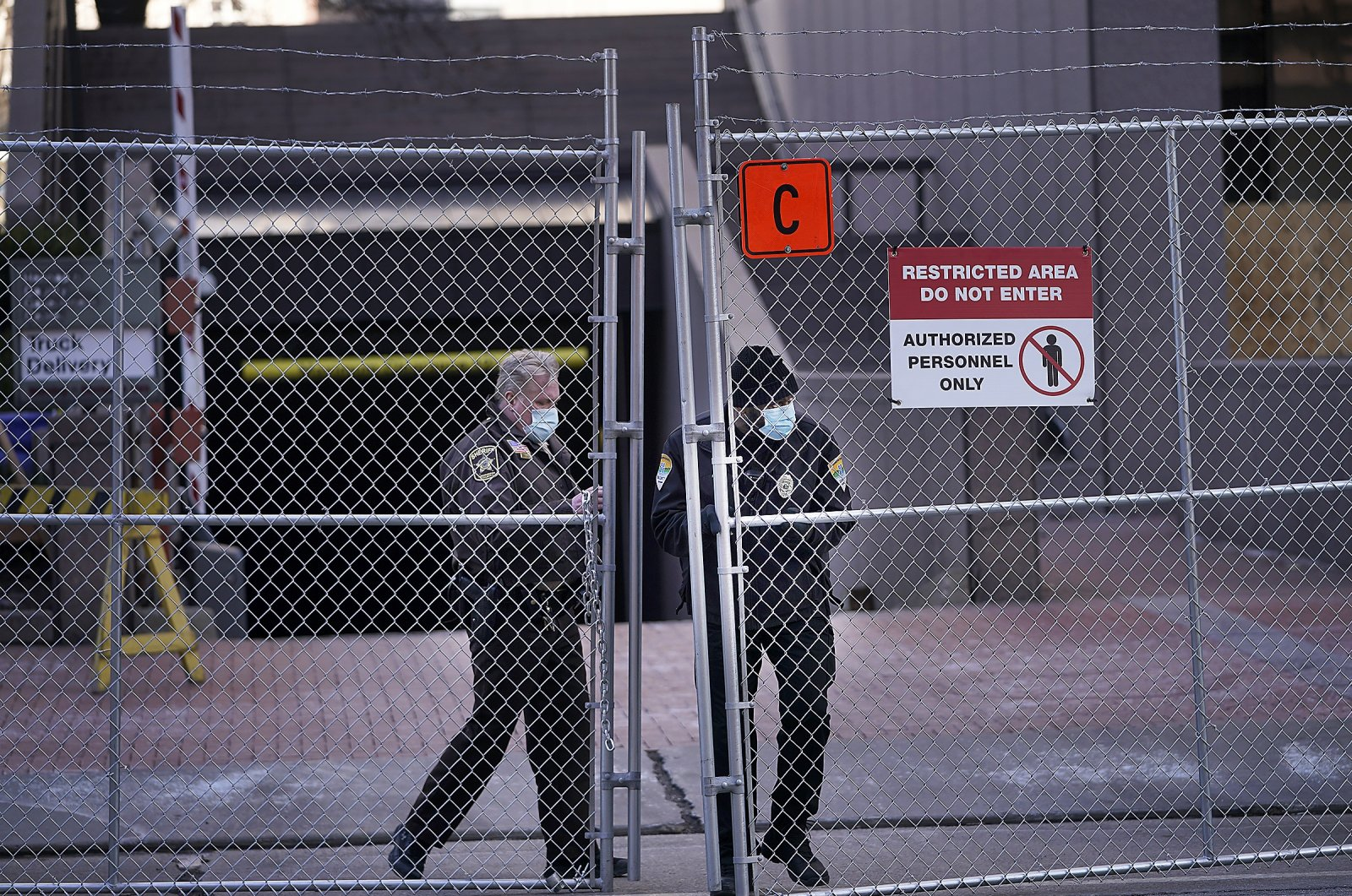 Law enforcement officers open a gate on a fenced perimeter outside the Hennepin County Government Center in Minneapolis, Minnesota, U.S., March 4, 2021. (Star Tribune via AP)