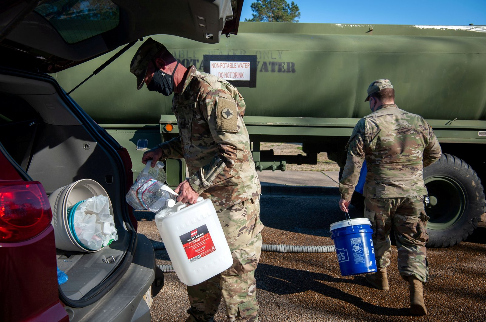 National Guard sergeants carry containers and a bucket to fill with water for a resident at a public water distribution site after cold weather caused large numbers of water outages in Jackson, Mississippi, U.S., March 4, 2021. (Reuters Photo)