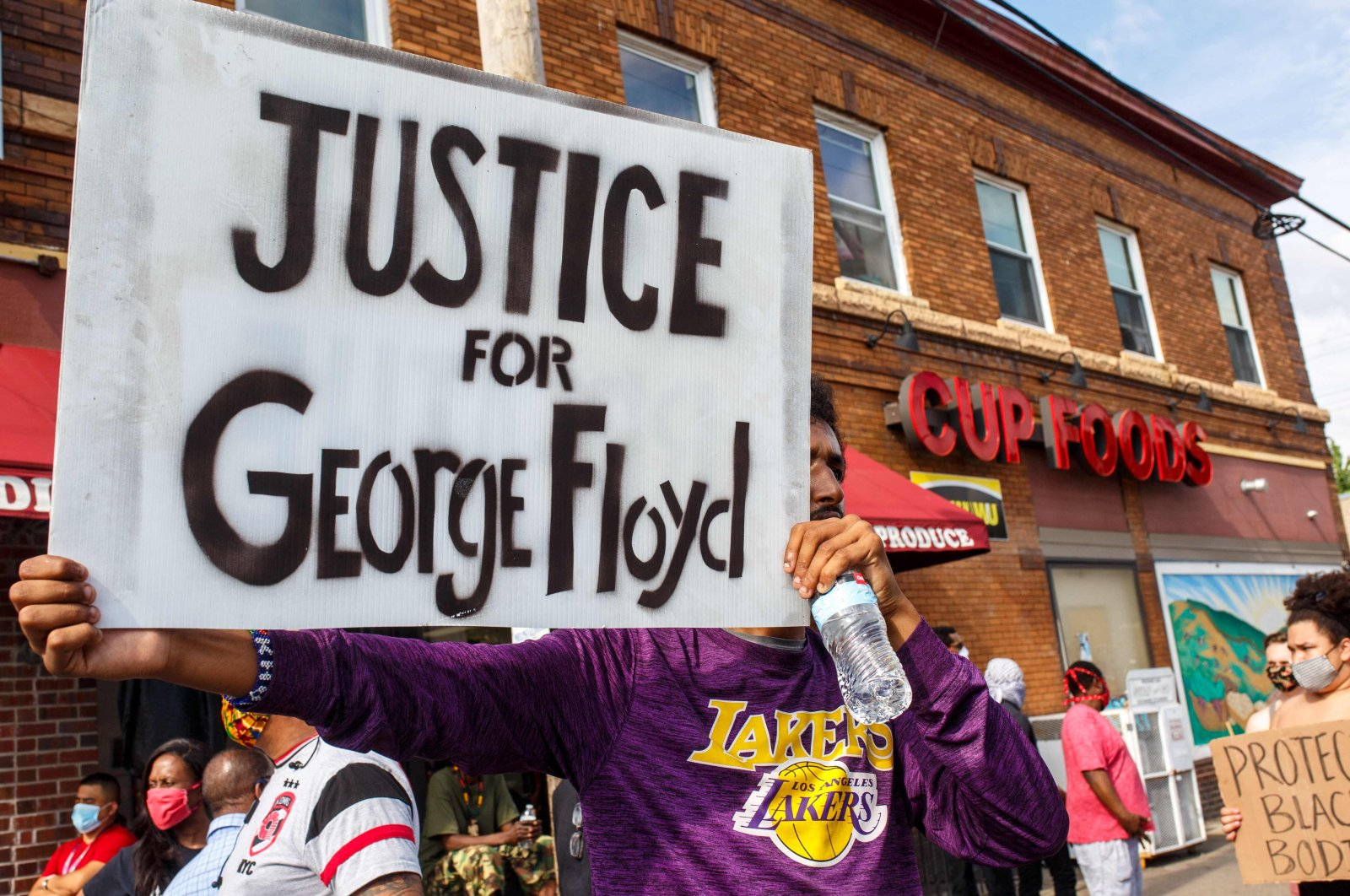 A man holds a sign while protesting near the area where a Minneapolis Police Department officer caused the death of George Floyd, Minneapolis, Minnesota, U.S., May 26, 2020. (AFP Photo)