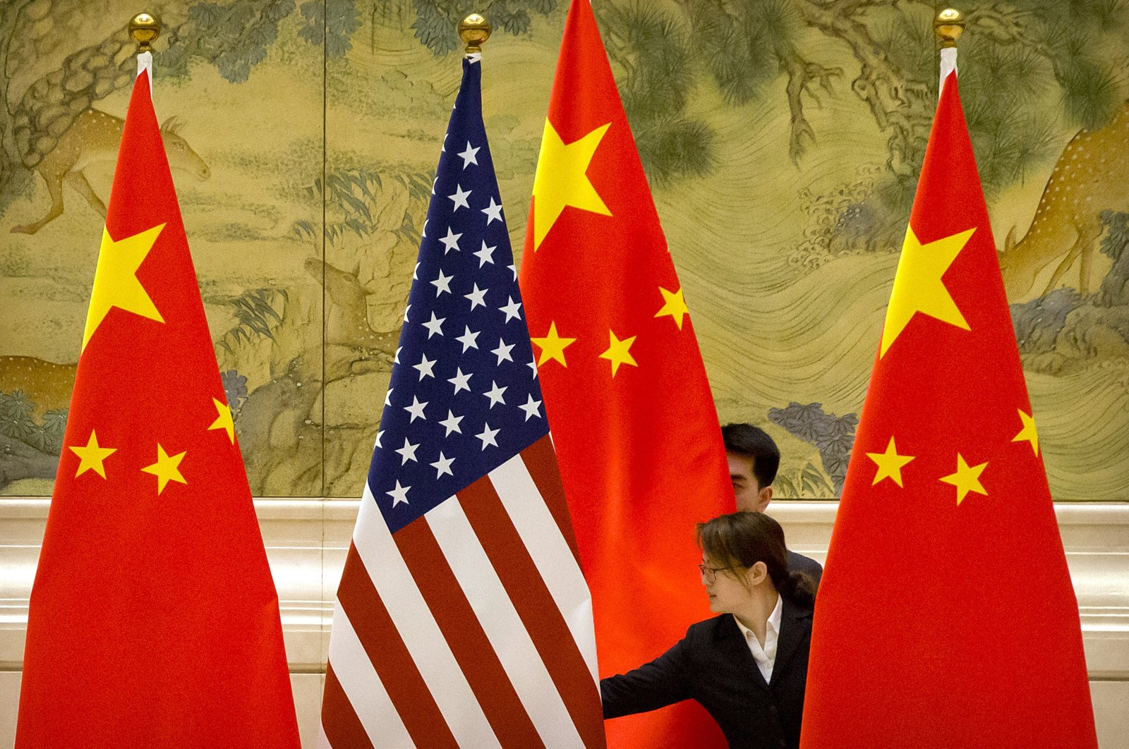 Chinese staffers adjust the U.S. and Chinese flags before the opening session of trade negotiations between U.S. and Chinese trade representatives at the Diaoyutai State Guesthouse in Beijing, Feb. 14, 2019. (AP Photo)